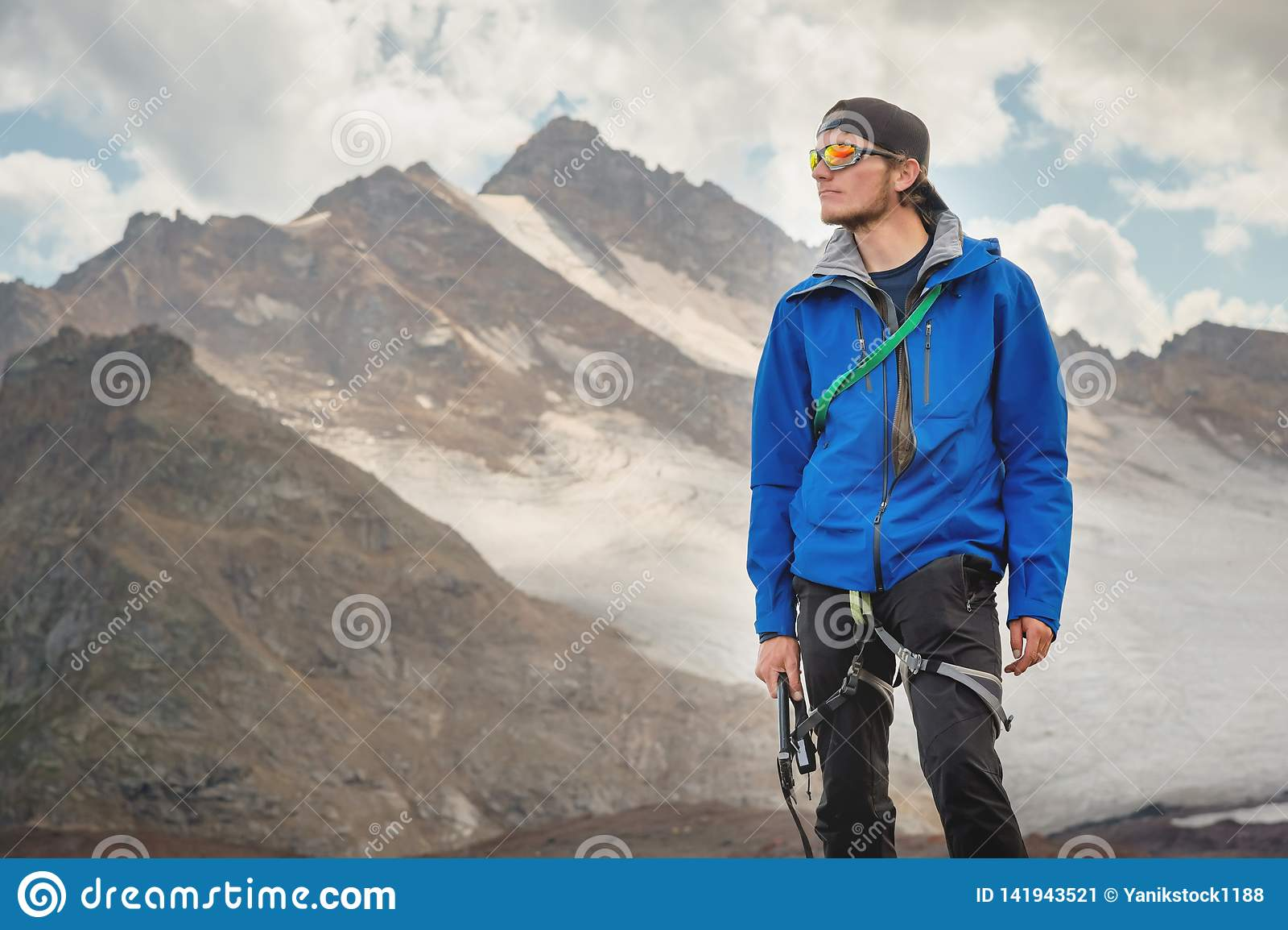 Portrait d un guide professionnel d un alpiniste dans un chapeau et des lunettes de soleil avec une hache de glace dans sa main c