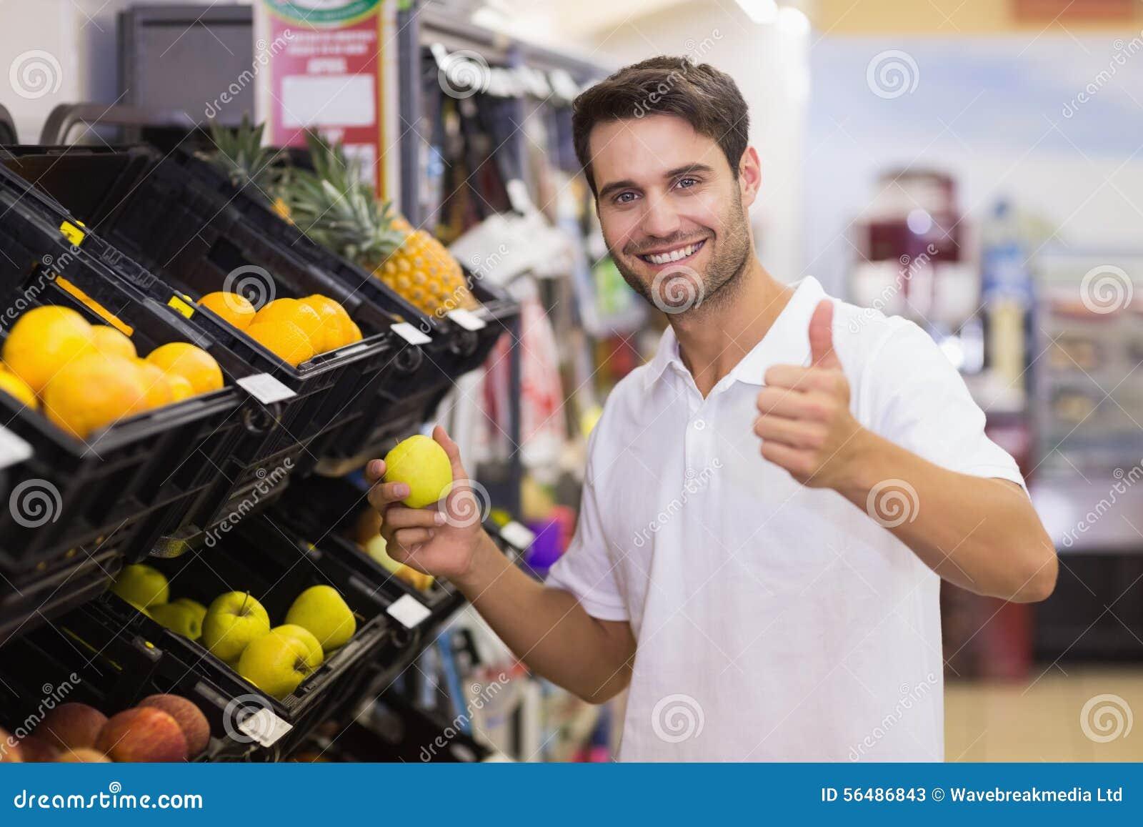 Portrait d un homme bel de sourire achetant un fruit avec le pouce