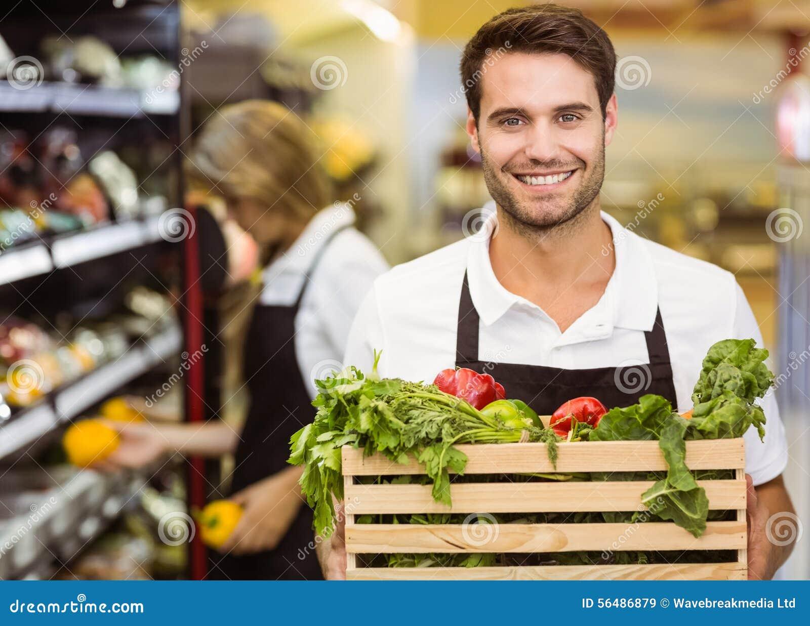 Portrait d un homme de sourire de personnel tenant une boîte de légumes frais