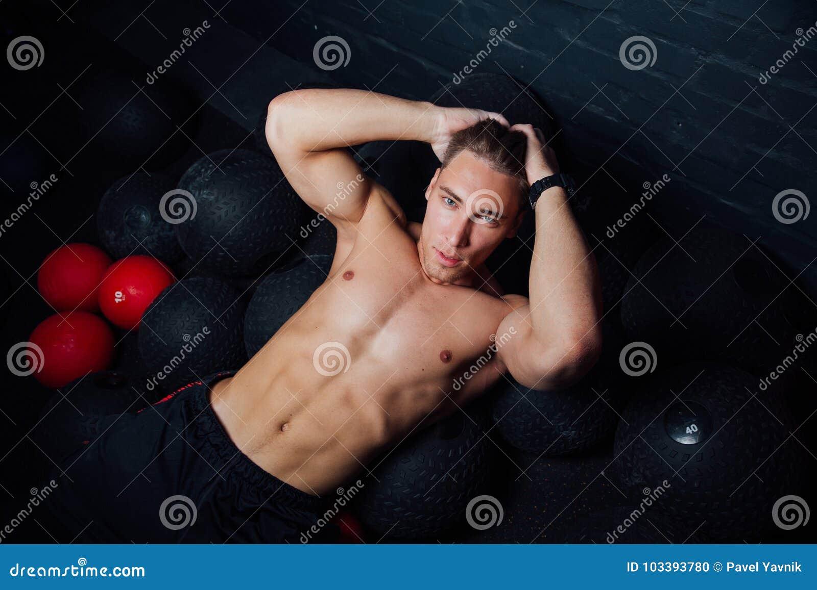 Portrait d un homme musculaire se reposant et se trouvant sur le plancher dans le gymnase de forme physique
