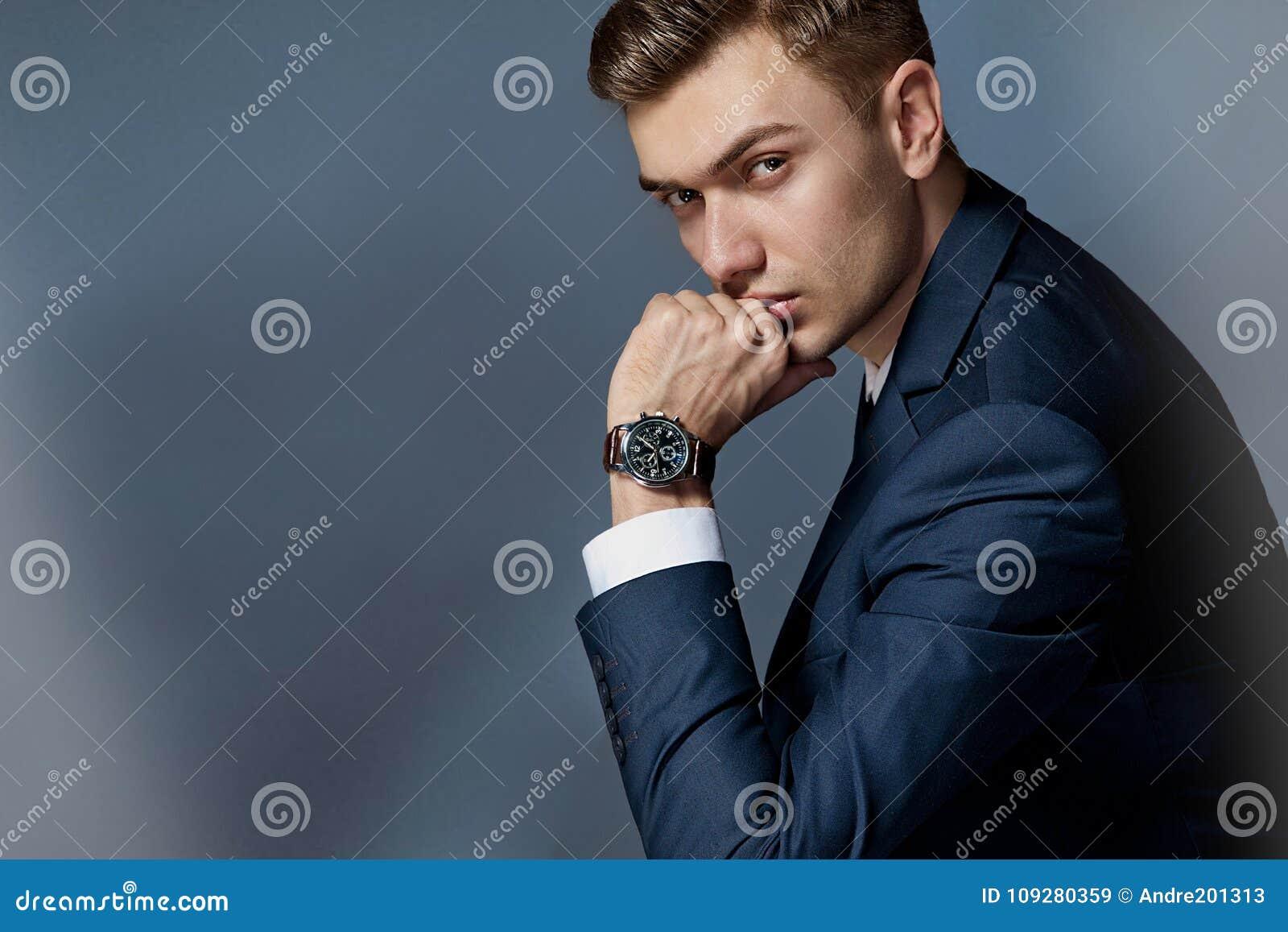 Portrait d un homme s asseyant avec un costume avec une montre, studio