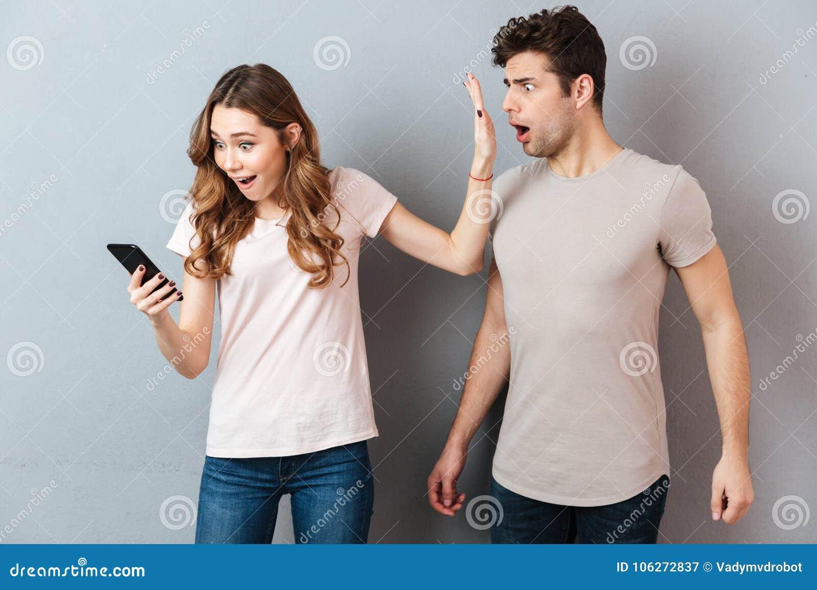 Portrait d un jeune couple se tenant avec le téléphone portable