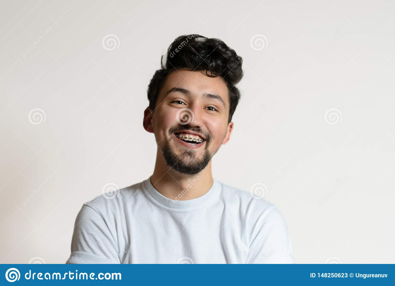 Portrait d un jeune homme avec des accolades souriant et riant Un jeune homme heureux avec des accolades sur un fond blanc