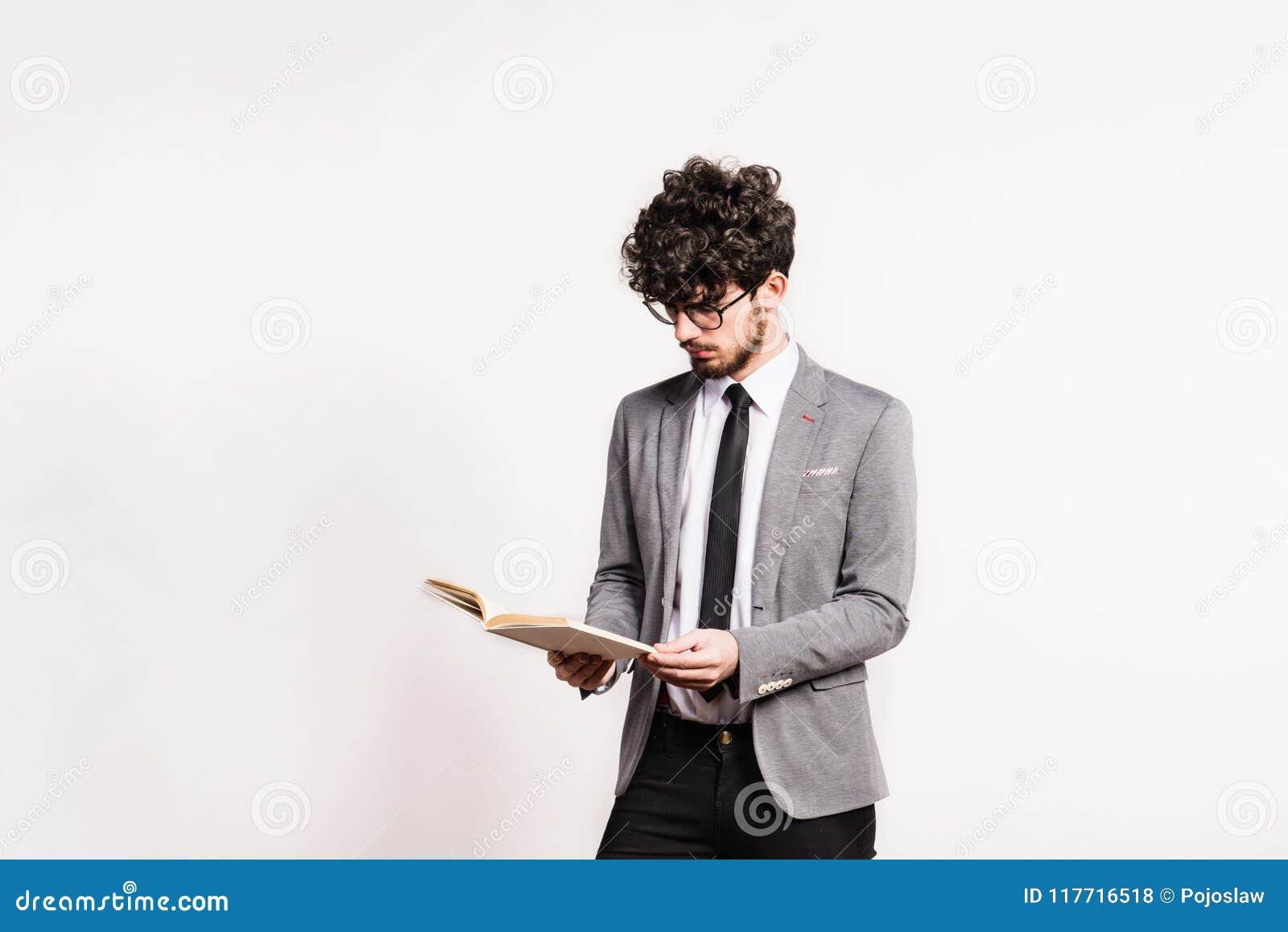 Portrait d un jeune homme avec un livre dans un studio sur un fond blanc
