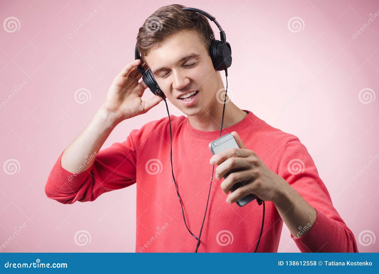 Portrait d un jeune homme bel avec des écouteurs souriant et écoutant une musique avec un smartphone