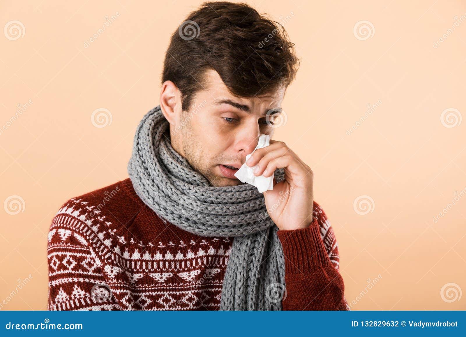 bbd981f8eaed Portrait d un jeune homme malade habillé dans le chandail et l écharpe  d isolement au-dessus du fond beige, tenant le tissu de papier, éternuant