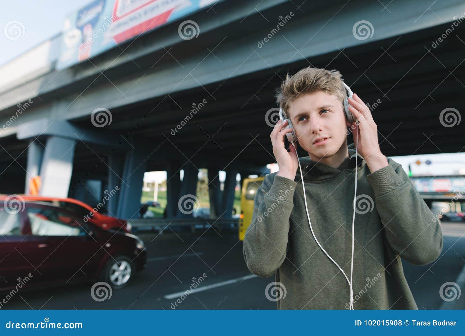 Portrait d un jeune homme marchant dans la ville sur le fond de l architecture urbaine et écoutant la musique dans des écouteurs