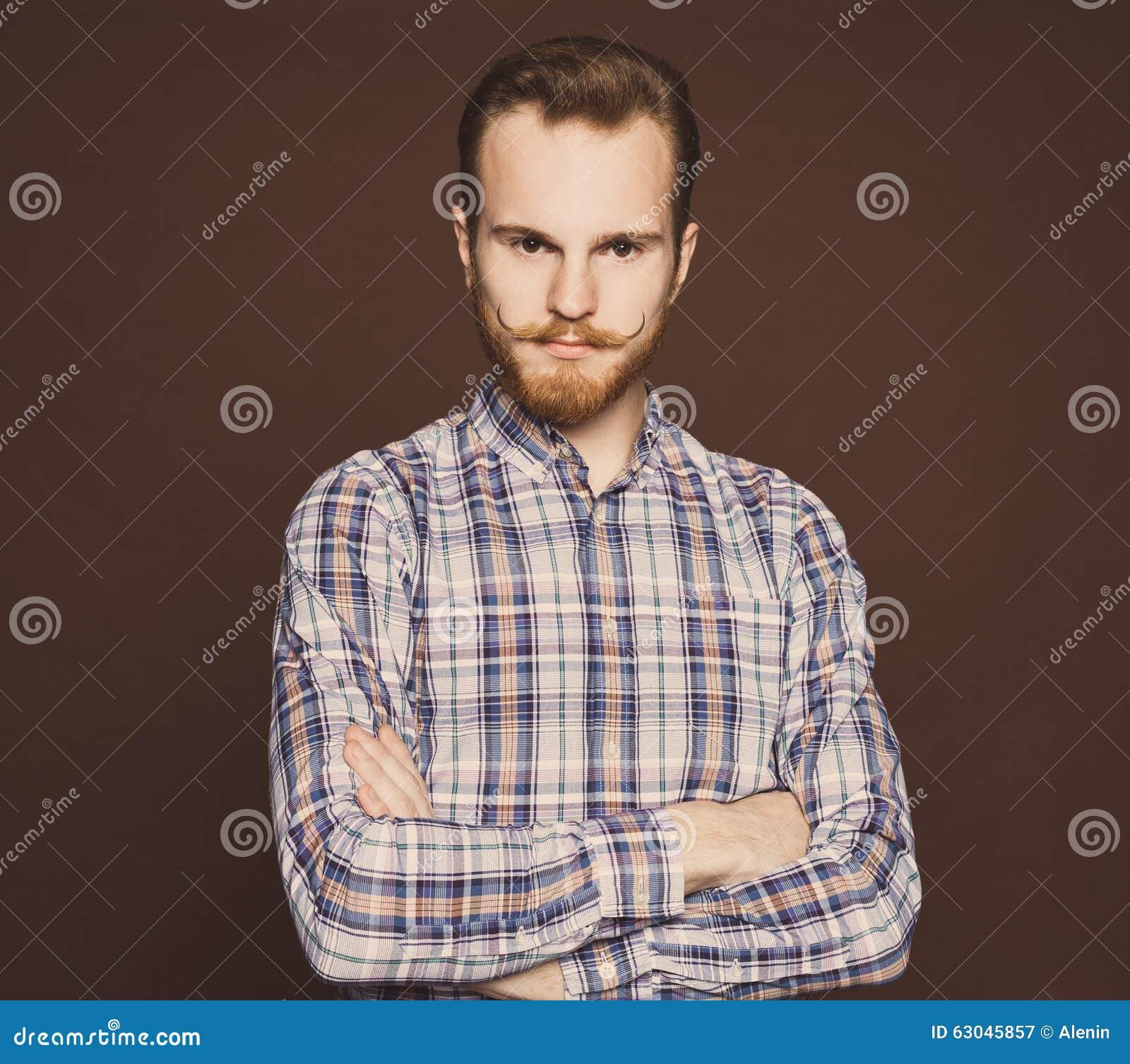portrait d 39 un jeune homme style avec de moustache et de barbe jeans et d 39 une chemise de plaid. Black Bedroom Furniture Sets. Home Design Ideas