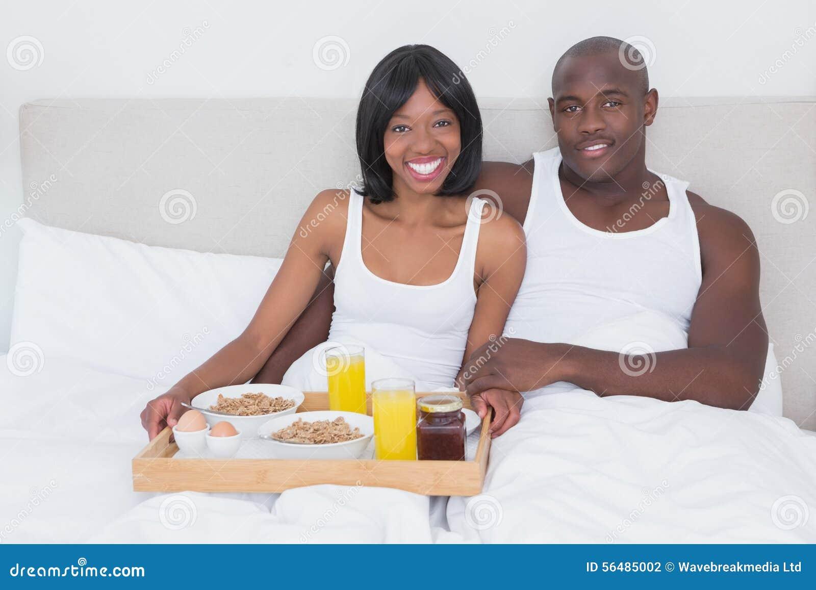Portrait d un joli couple prenant le petit déjeuner dans le lit ensemble