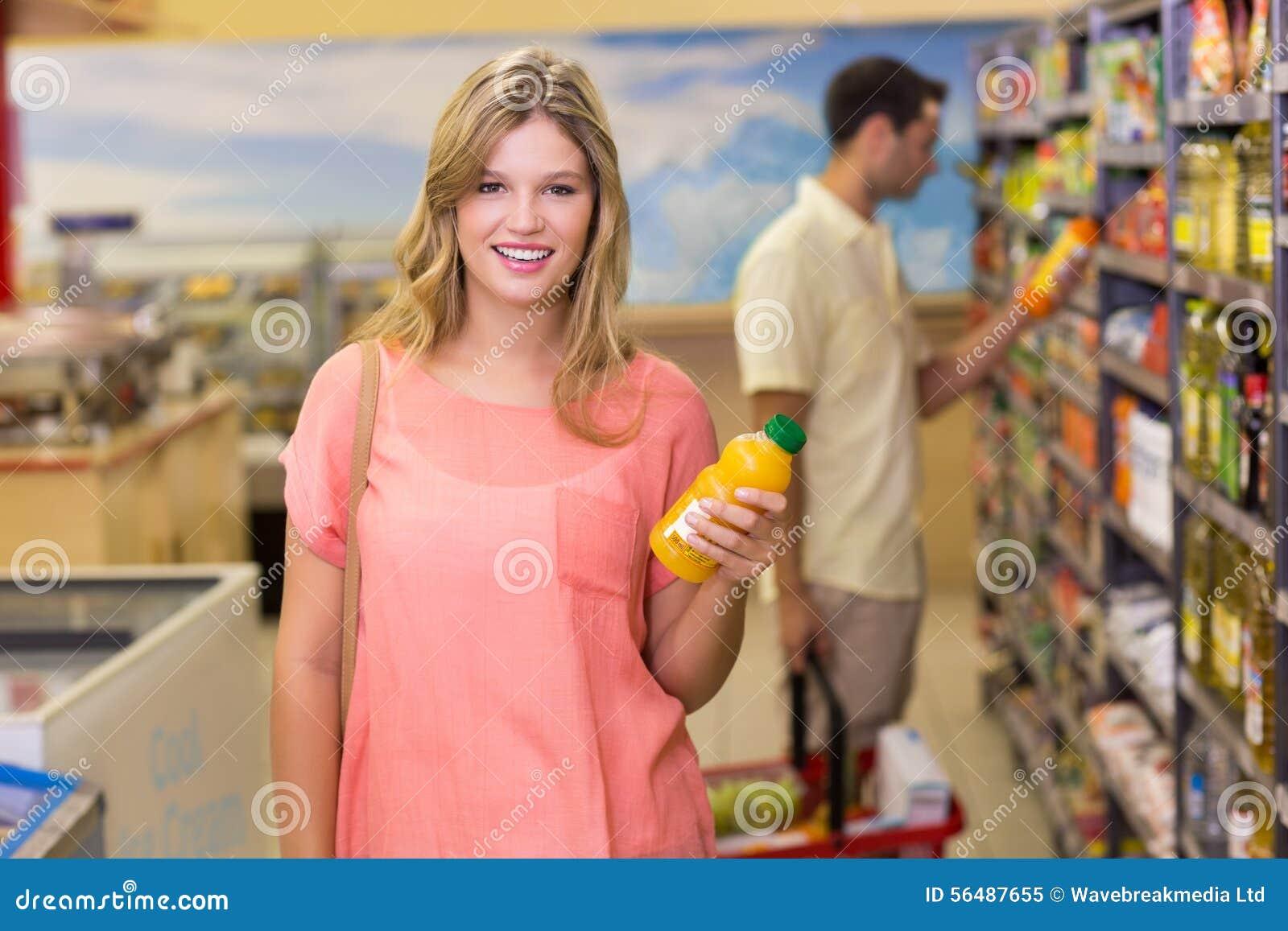 Portrait d un joli produit de achat de sourire de femme blonde