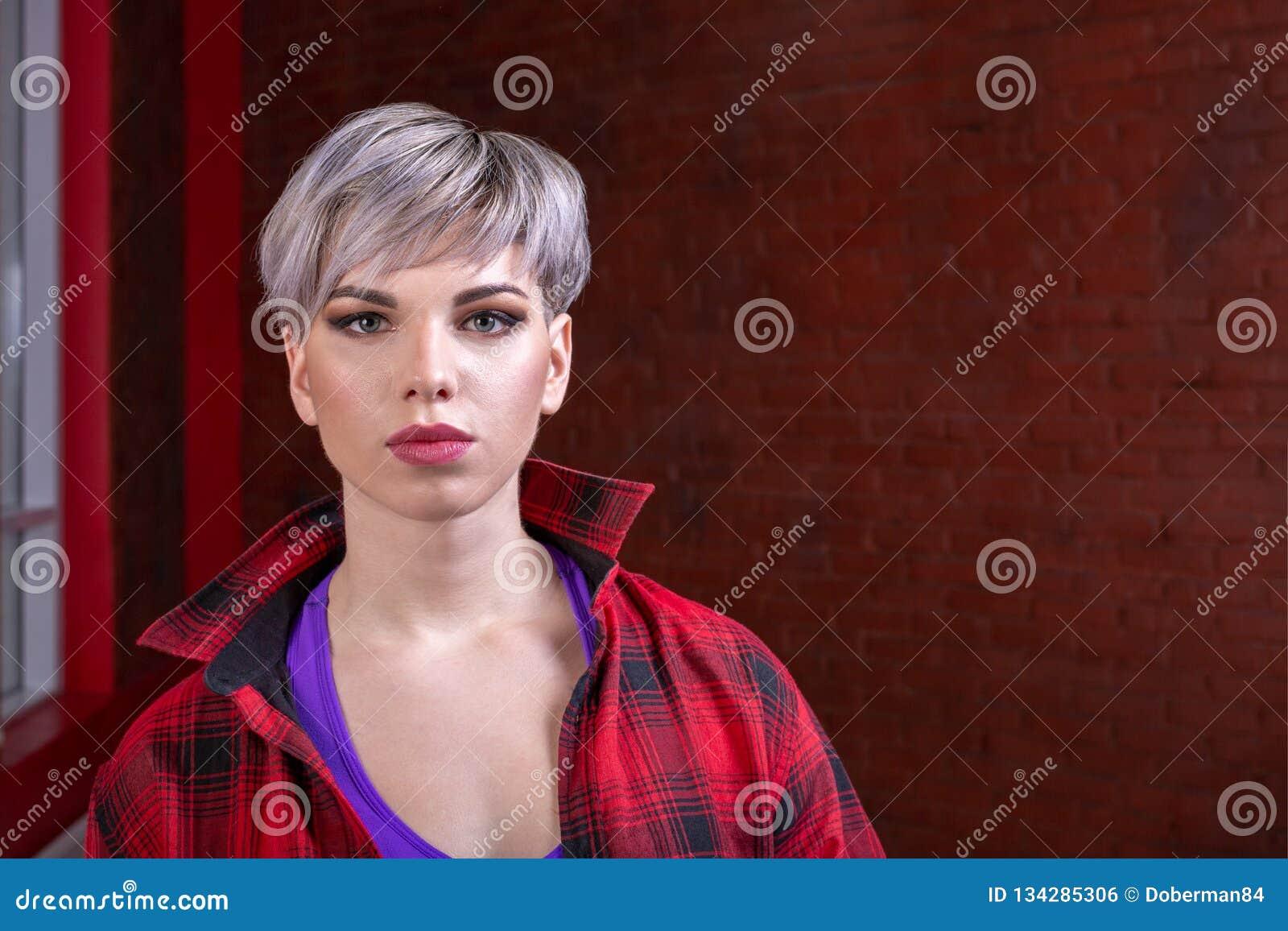 Portrait d un plan rapproché de fille d une belle jeune blonde sexy avec les cheveux courts dans une chemise de plaid rouge, hipp