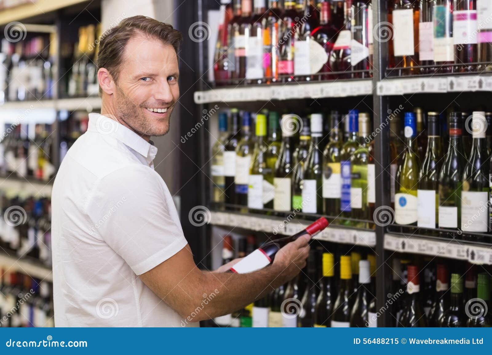 Portrait d un sourire beau ayant une bouteille de vin dans des ses mains