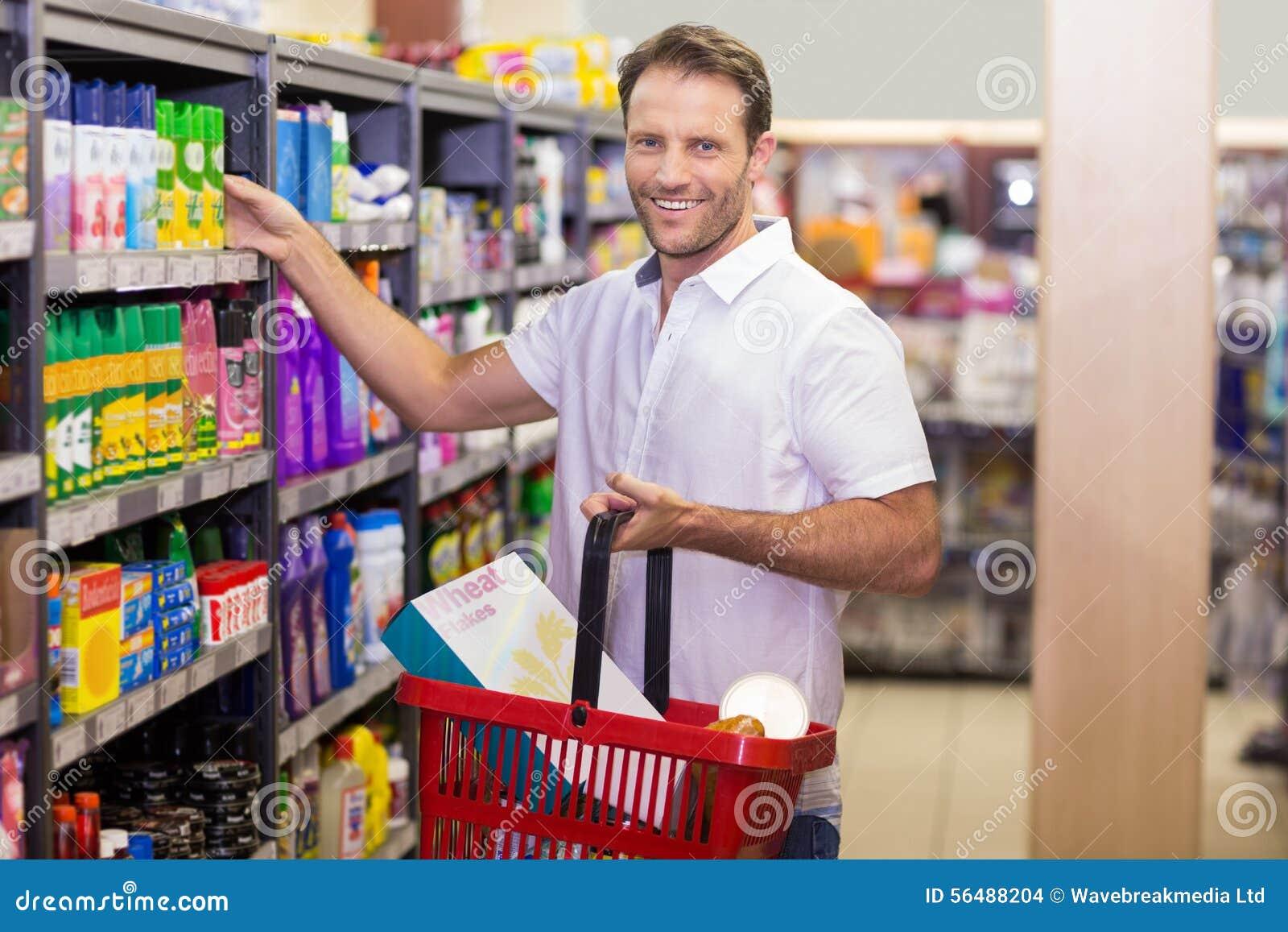 Portrait d un sourire beau prenant un produit dans l étagère