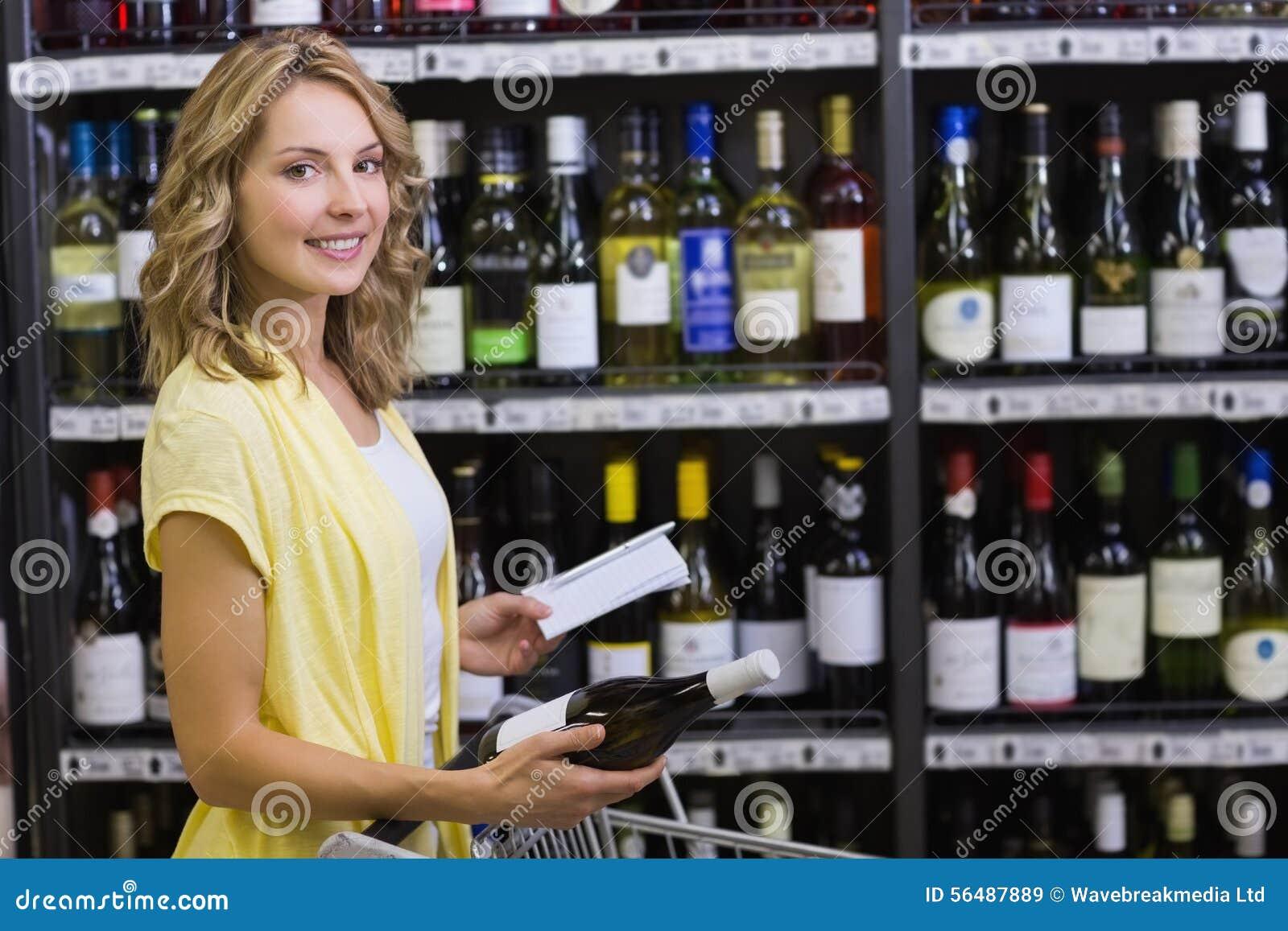 Portrait d un sourire femme assez blonde ayant dans des ses mains une bouteille et un bloc-notes de vin