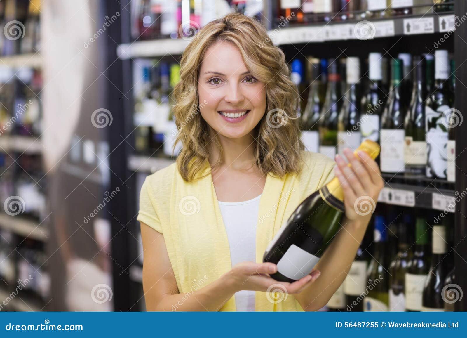 Portrait d un sourire femme assez blonde ayant une bouteille de vin