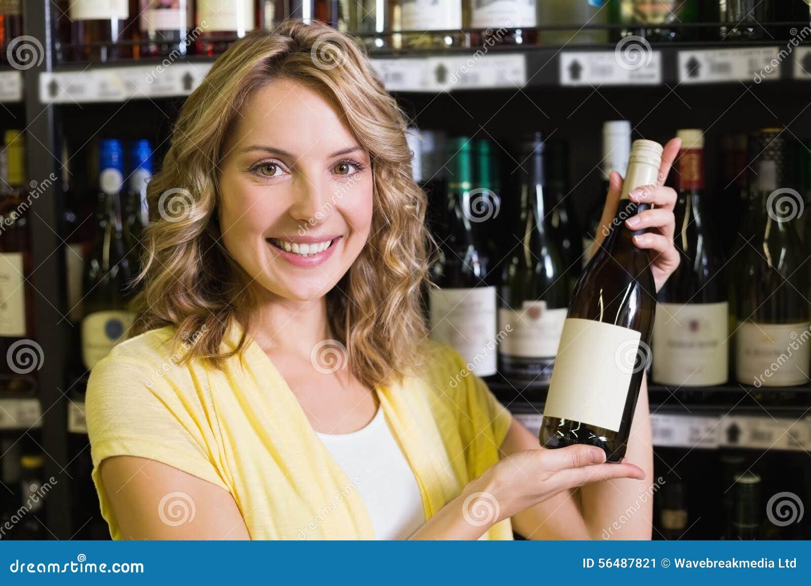 Portrait d un sourire femme assez blonde montrant une bouteille de vin