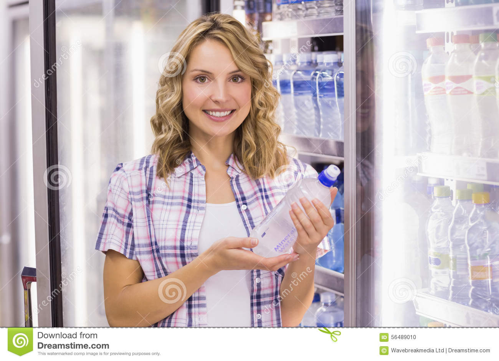 Portrait d un sourire femme assez blonde prenant une bouteille d eau