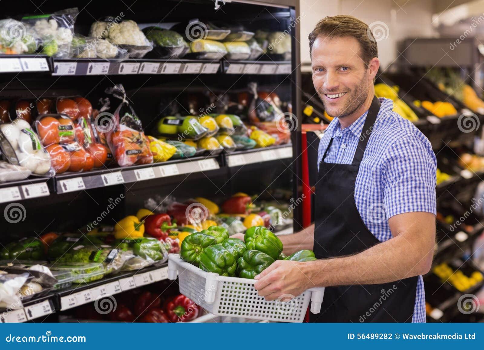 Portrait d un travailleur beau de sourire tenant une boîte avec des légumes