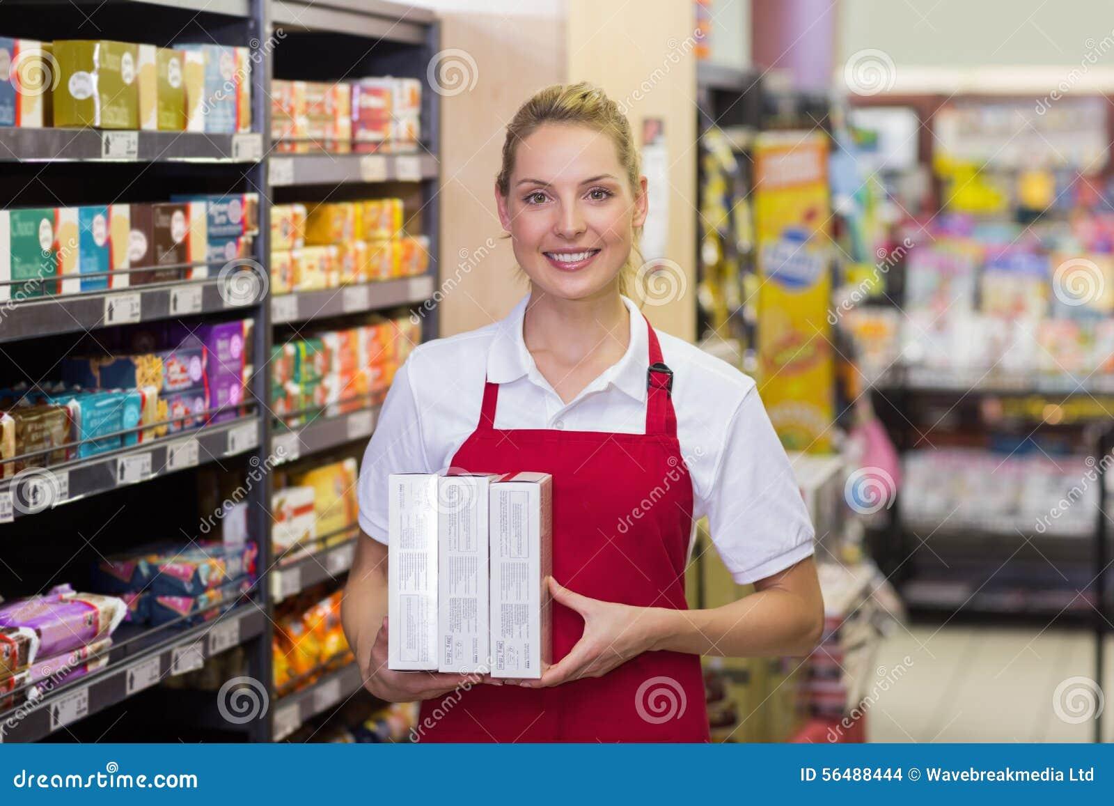 Portrait d un travailleur blond de sourire ayant des produits