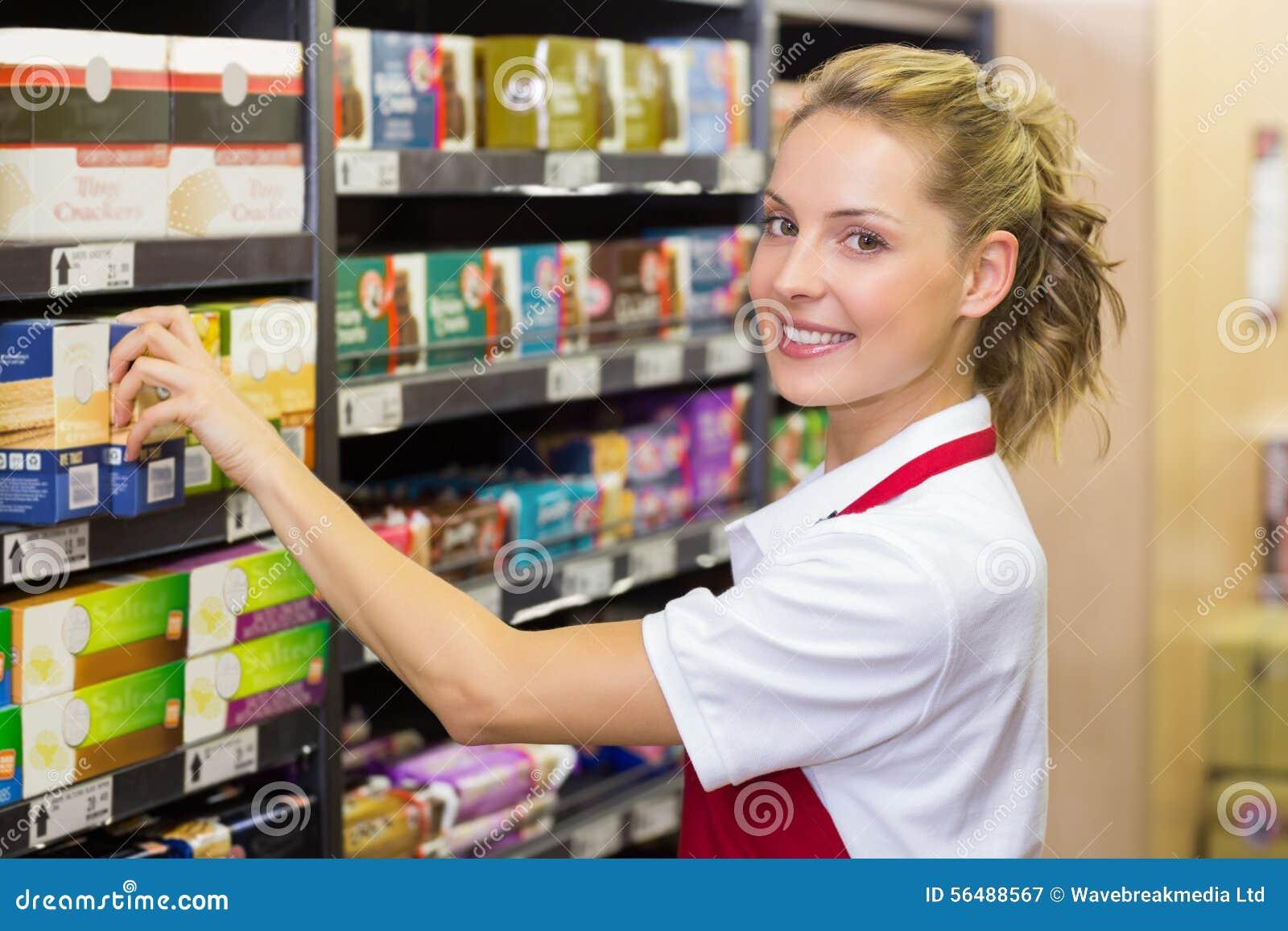 Portrait d un travailleur de sourire prenant un produit dans l étagère