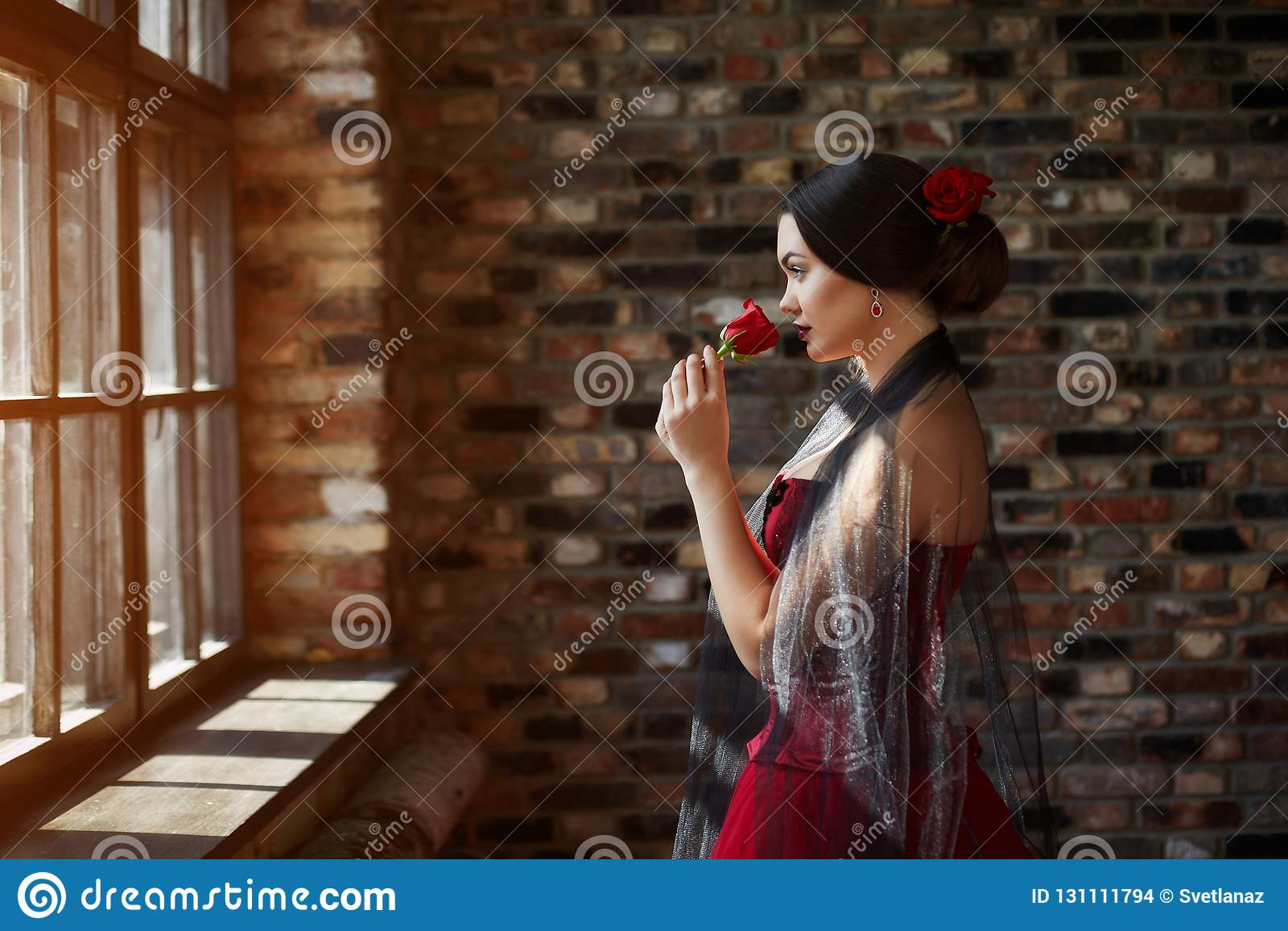 Portrait d une belle danseuse de jeune femme dans une robe rouge près de la fenêtre