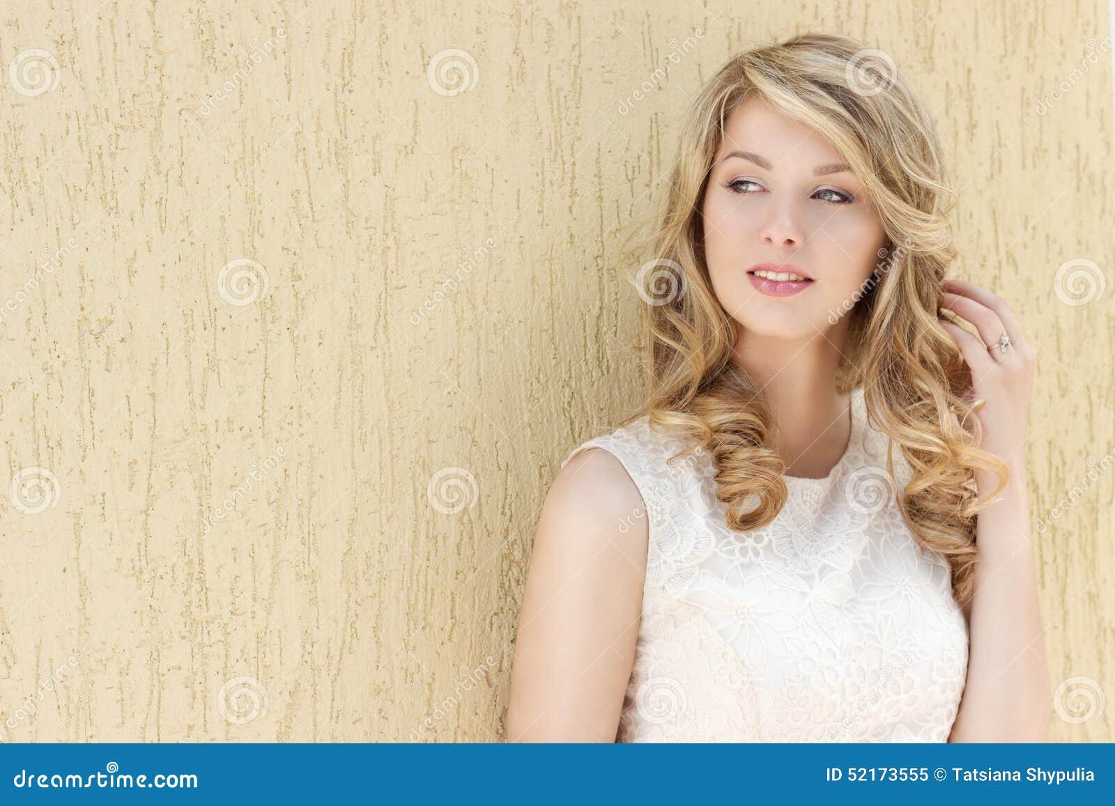 Portrait d une belle fille heureuse de sourire sexy avec de grandes pleines lèvres avec les cheveux blonds dans une robe blanche