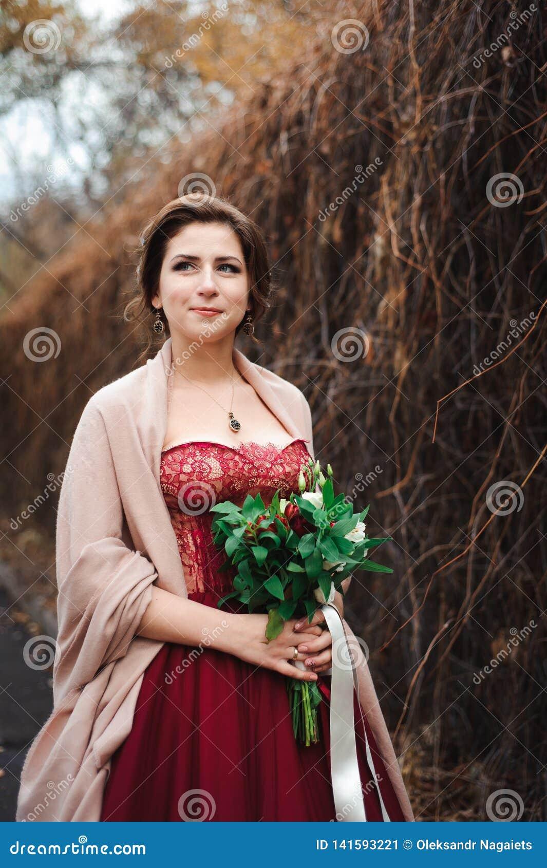 Portrait d une belle jeune mariée dans une robe rouge avec un bouquet l épousant dans une main