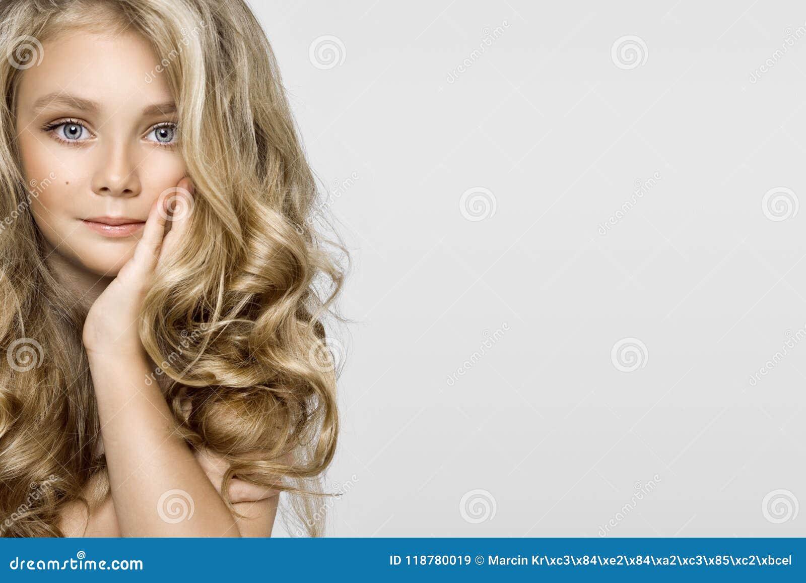 Portrait d une belle petite fille avec de longs cheveux sur un fond blanc dans le studio