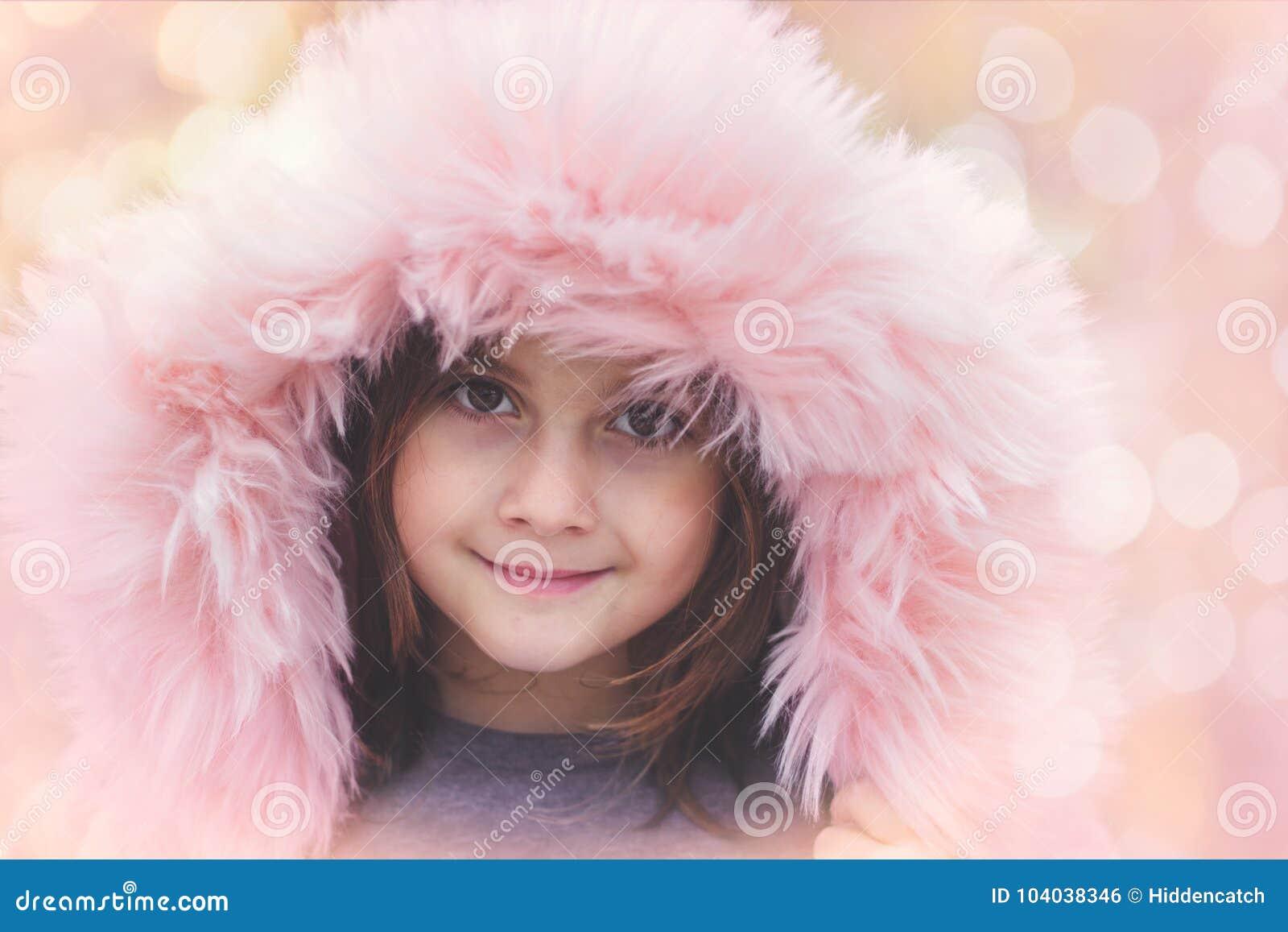 Portrait d une belle petite fille avec le capot rose de fourrure