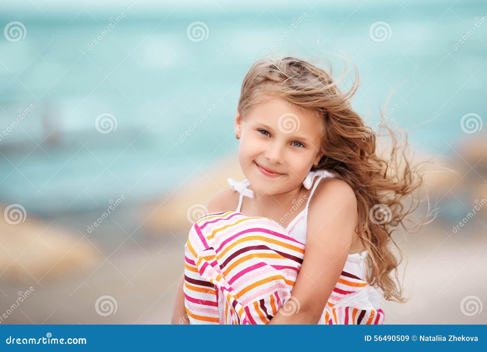 Portrait d une belle petite fille blonde sur la plage à un tro