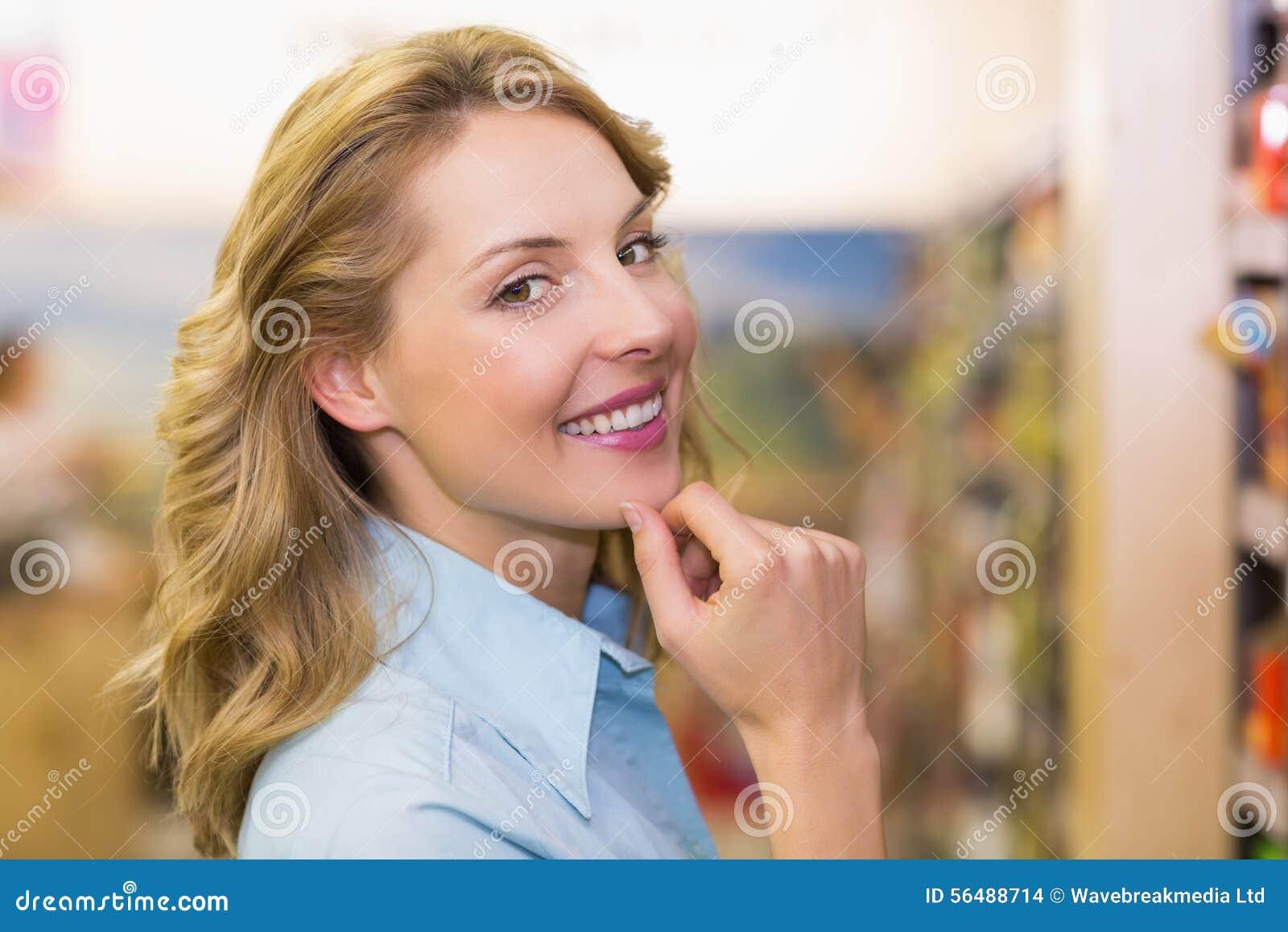 Portrait d une femme blonde de sourire avec des mains sur le menton