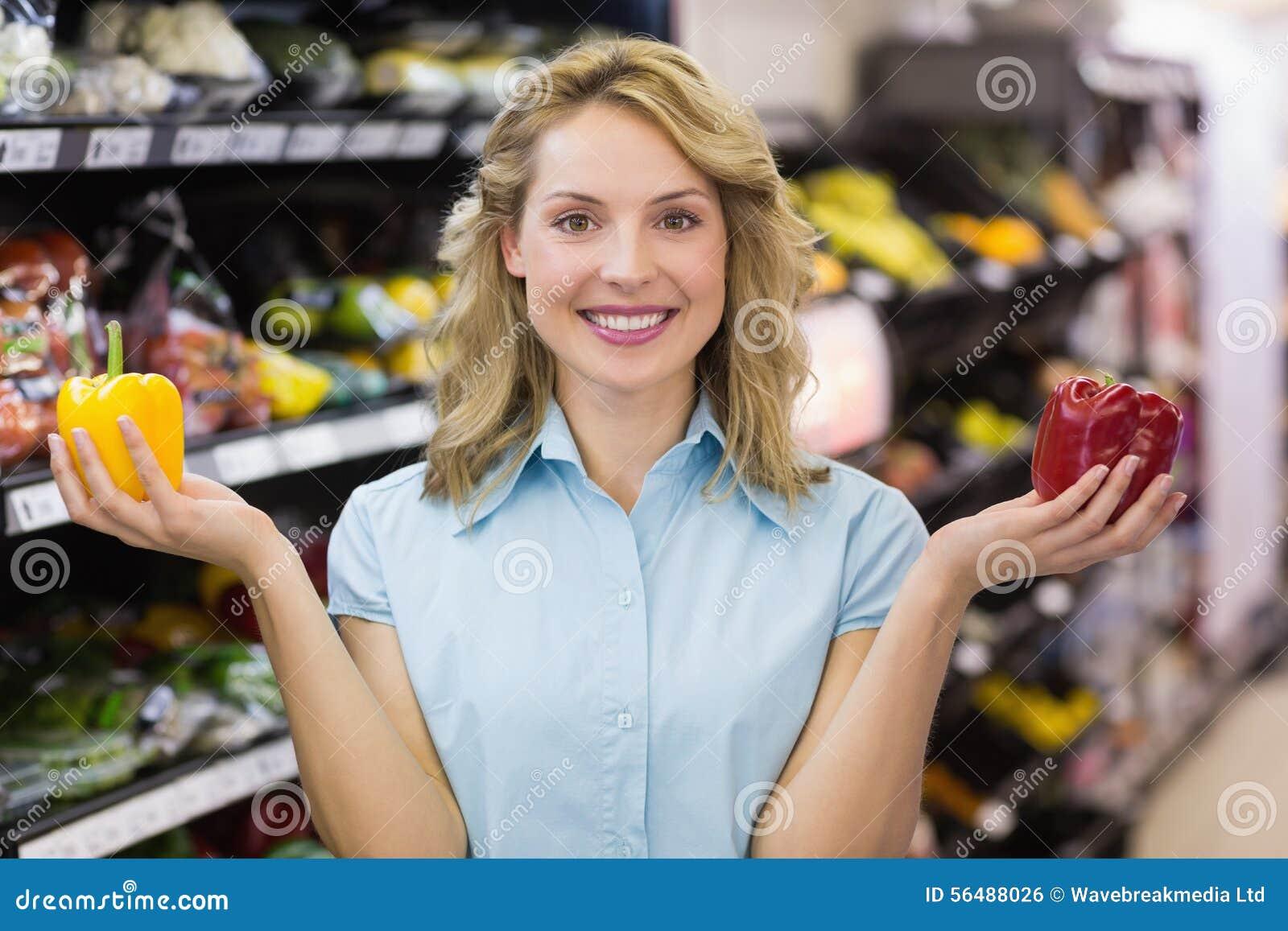Portrait d une femme blonde de sourire ayant un légume sur ses mains