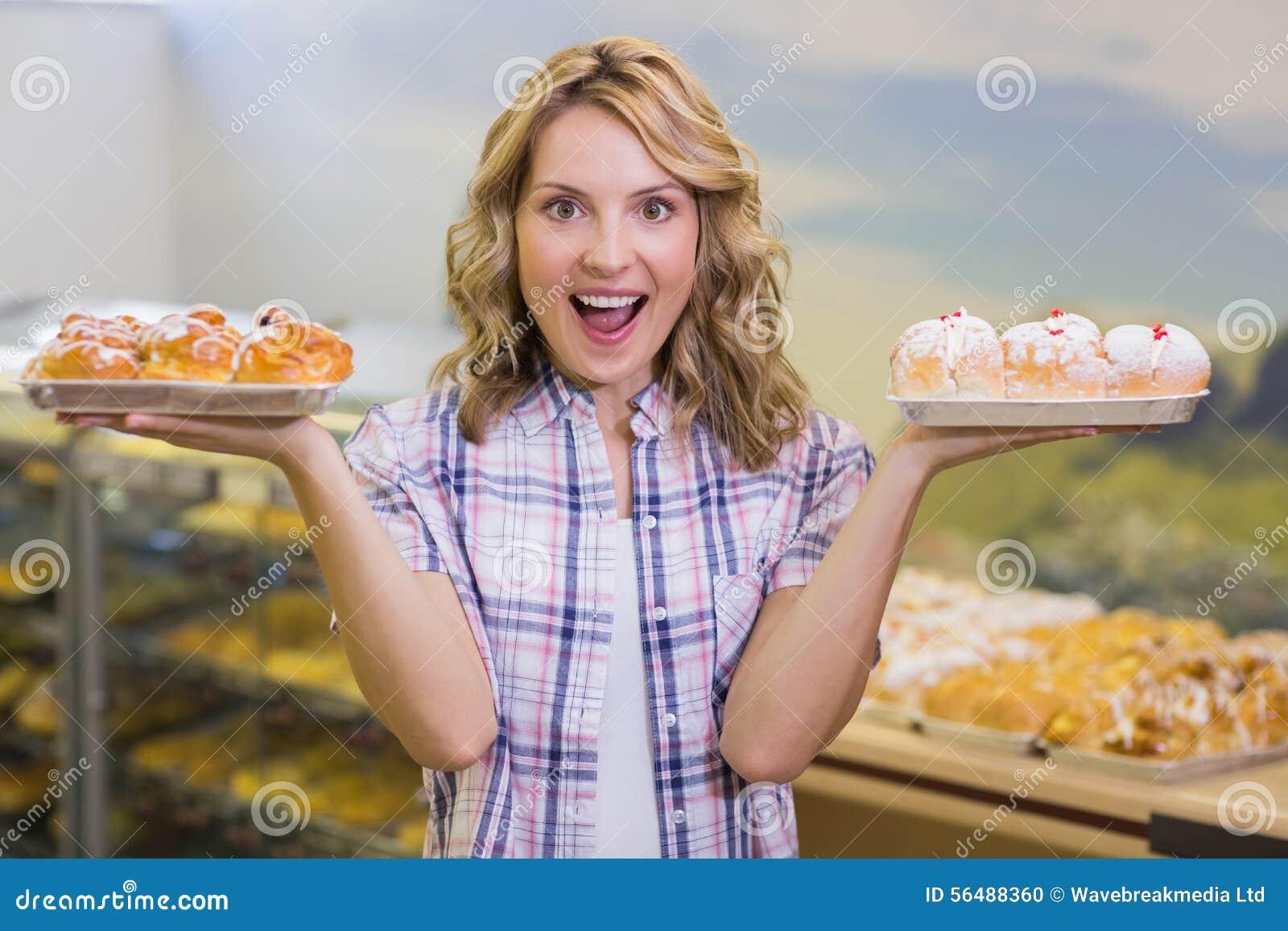 Portrait d une femme blonde de sourire ayant une pâtisserie