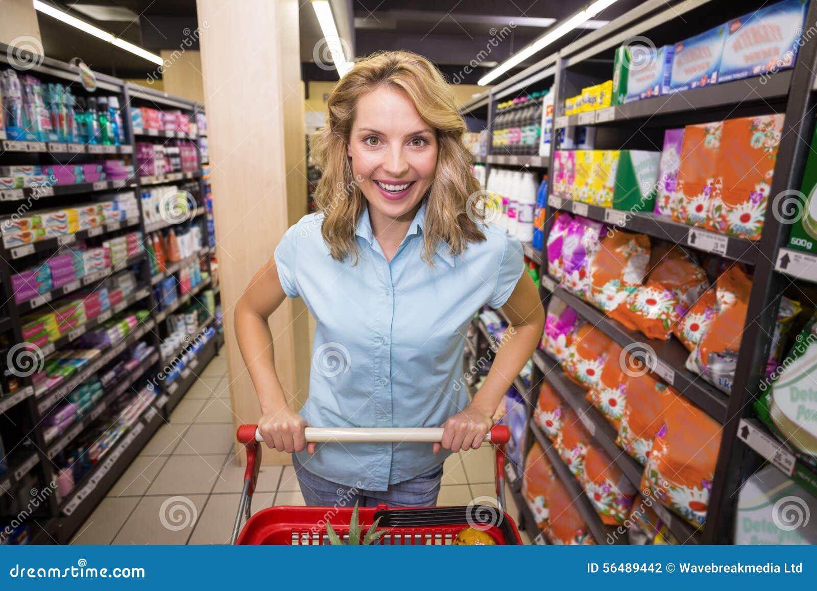 Portrait d une femme blonde de sourire dans le bas-côté avec son chariot