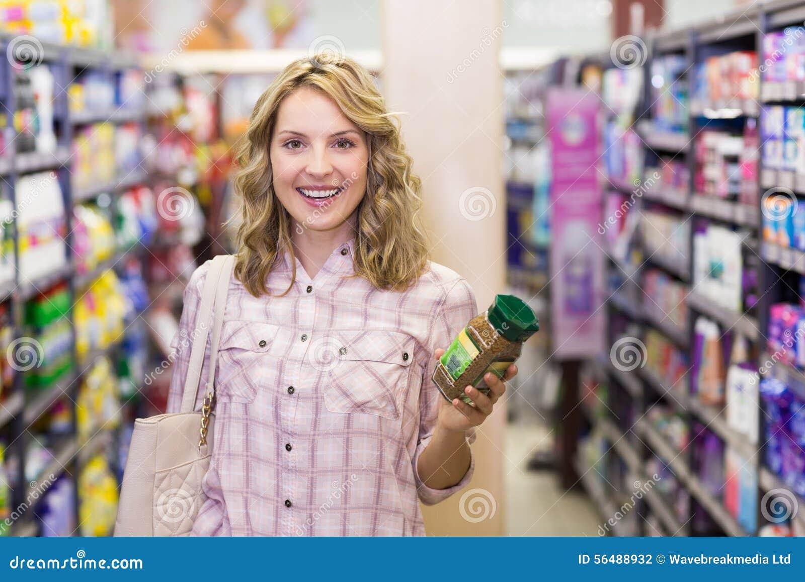 Portrait d une femme blonde de sourire heureuse ayant un produit dans des ses mains