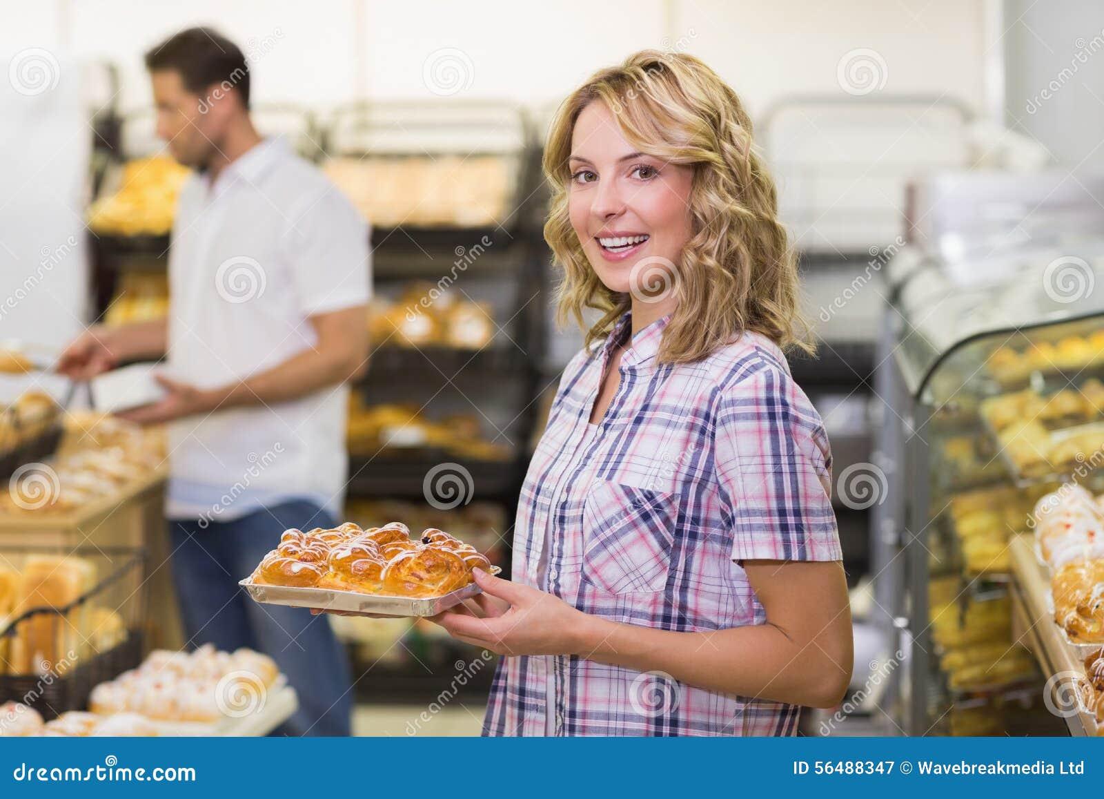 Portrait d une femme blonde de sourire prenant une pâtisserie