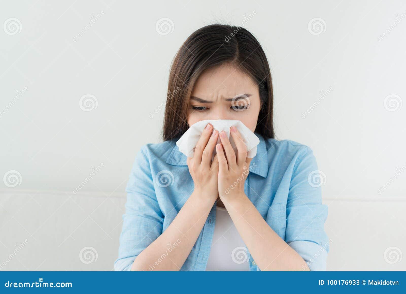 Portrait d une femme malade soufflant son nez tout en se reposant sur le s