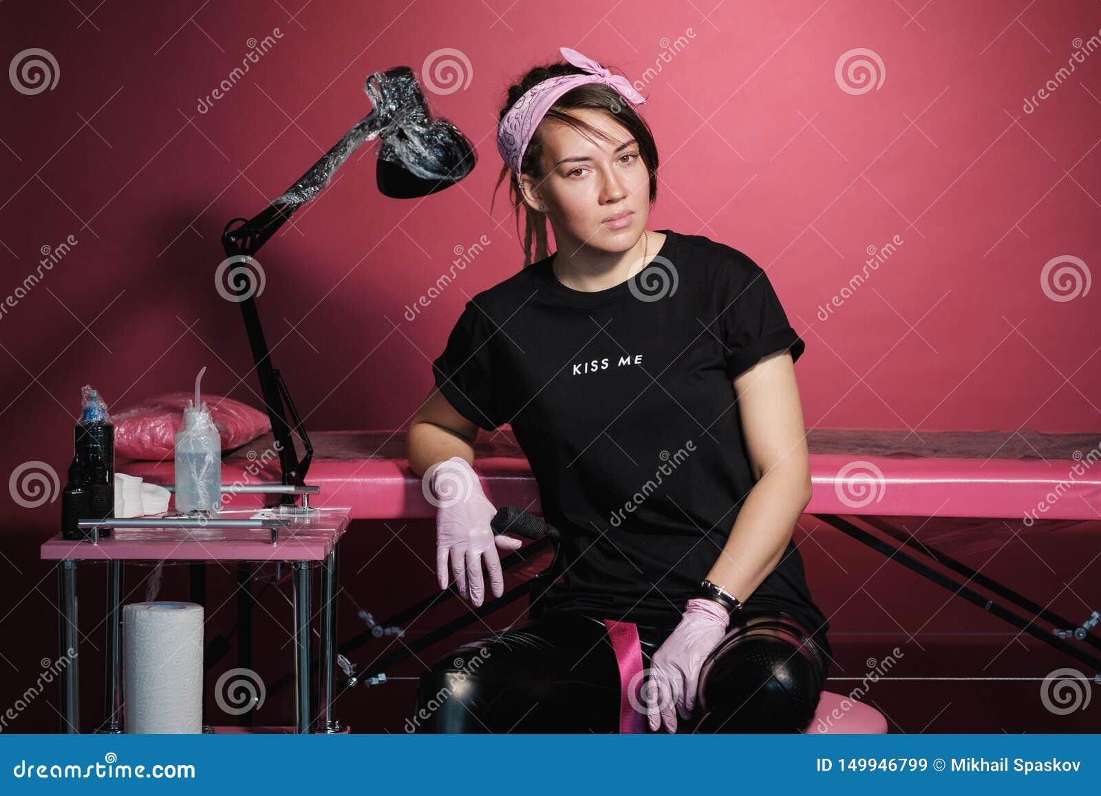Portrait d une femme professionnelle de maître de tatouage Vêtements noirs, et dreadlocks blanc rouge-rose de fond Endroit de
