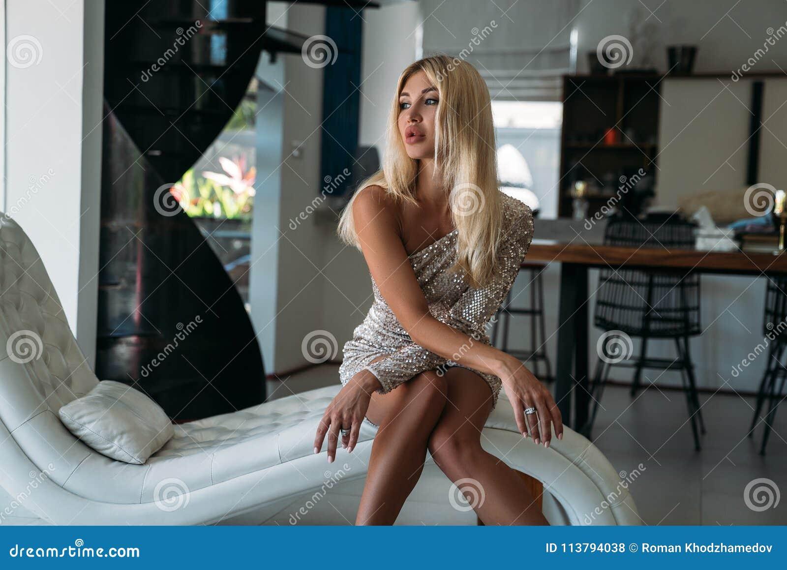 Portrait d une fille blonde mignonne avec de grandes belles lèvres se reposant sur le sofa La fille dans une robe brillante de di