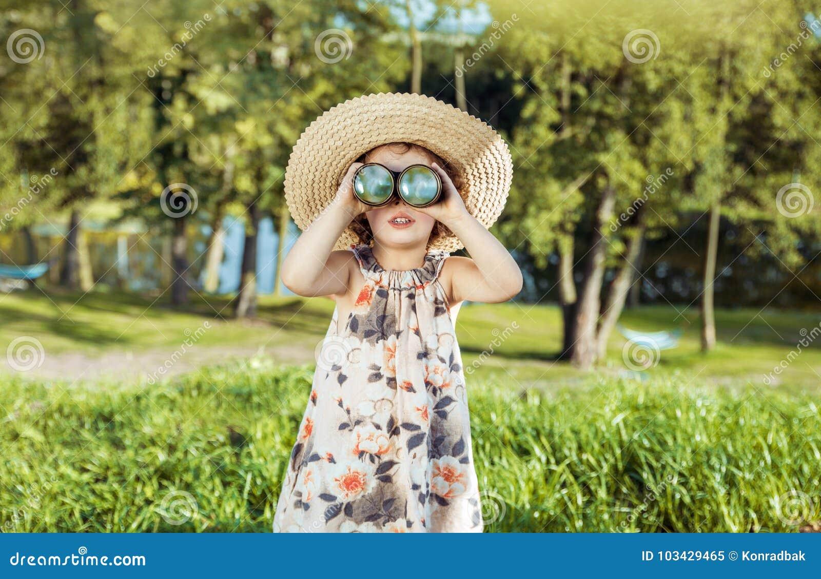 Portrait d une fille gaie et petite regardant par le binocula