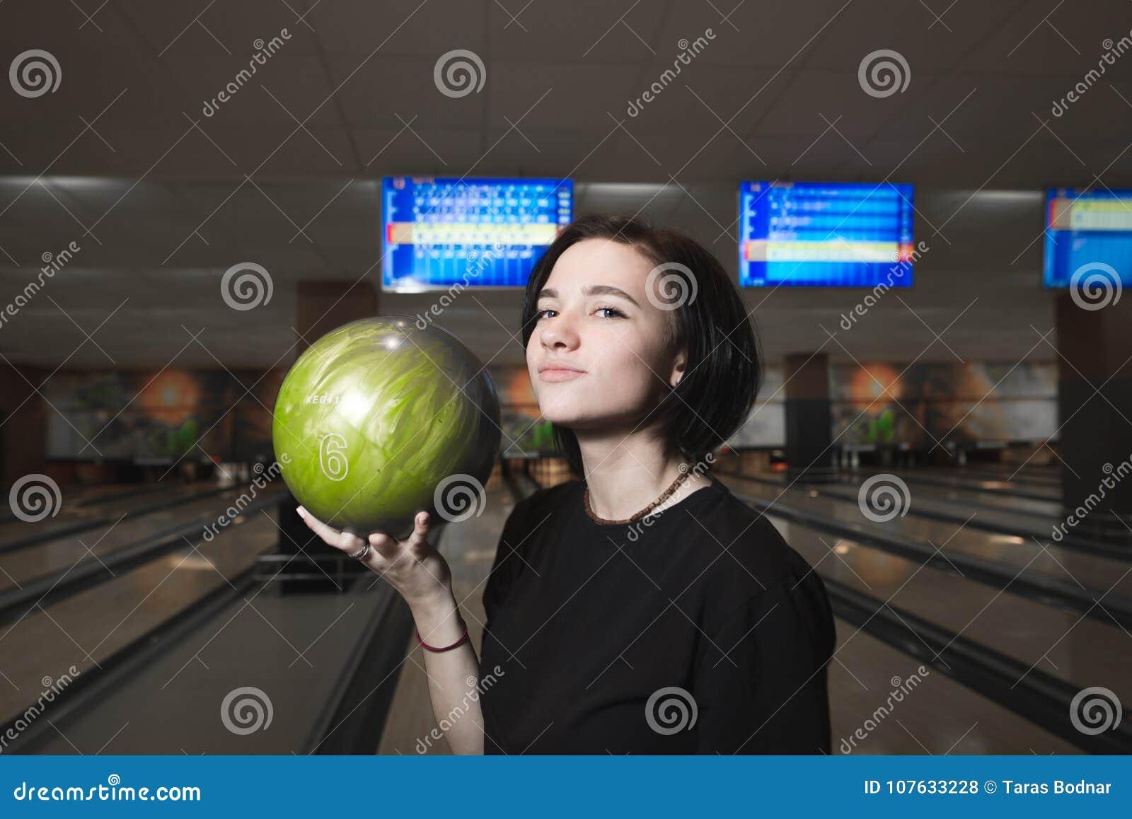 Portrait d une fille positive jouant le club de bowling Fille avec la boule de bowling dans des ses mains
