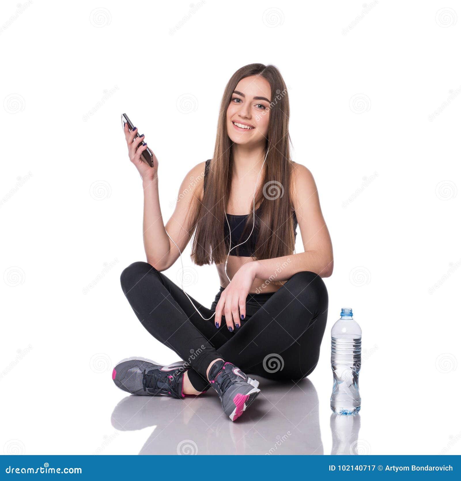 Portrait d une jeune femme d athlète écoutant la musique avec des écouteurs au-dessus du fond blanc Causerie attrayante de fille