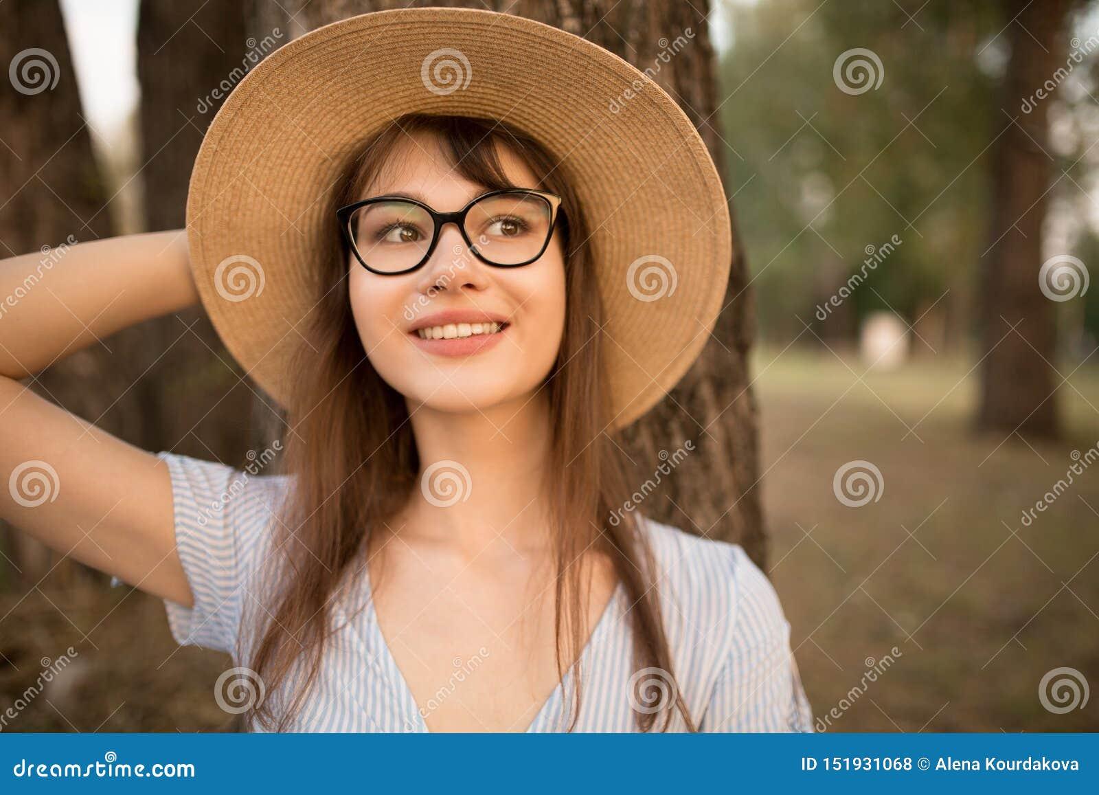 Portrait d une jeune femme attirante en parc Brune heureuse dans un chapeau avec les verres et la robe