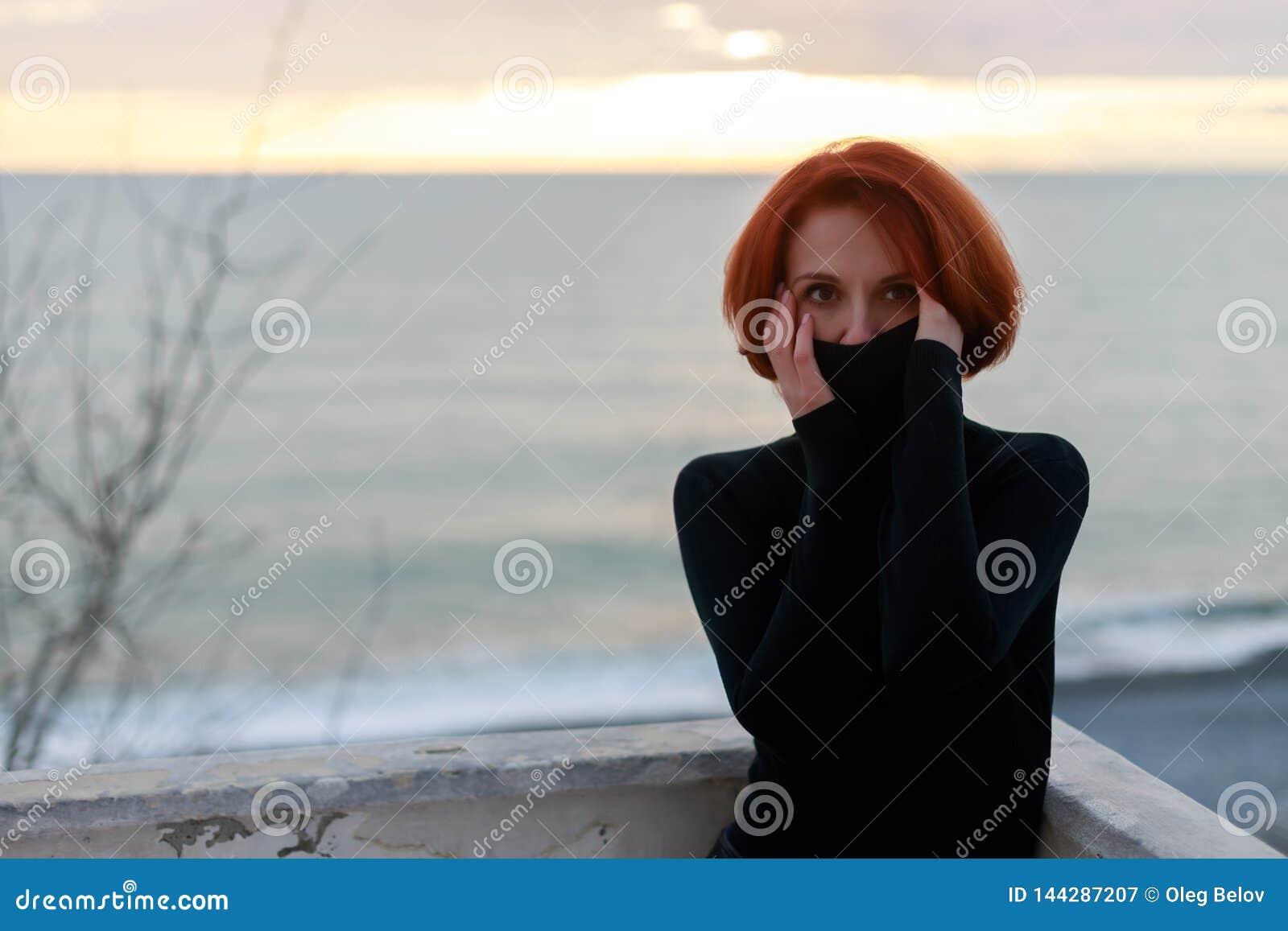 Portrait d une jeune femme avec les cheveux rouges avec un regard agité sur le fond de la mer et du coucher du soleil au printemp