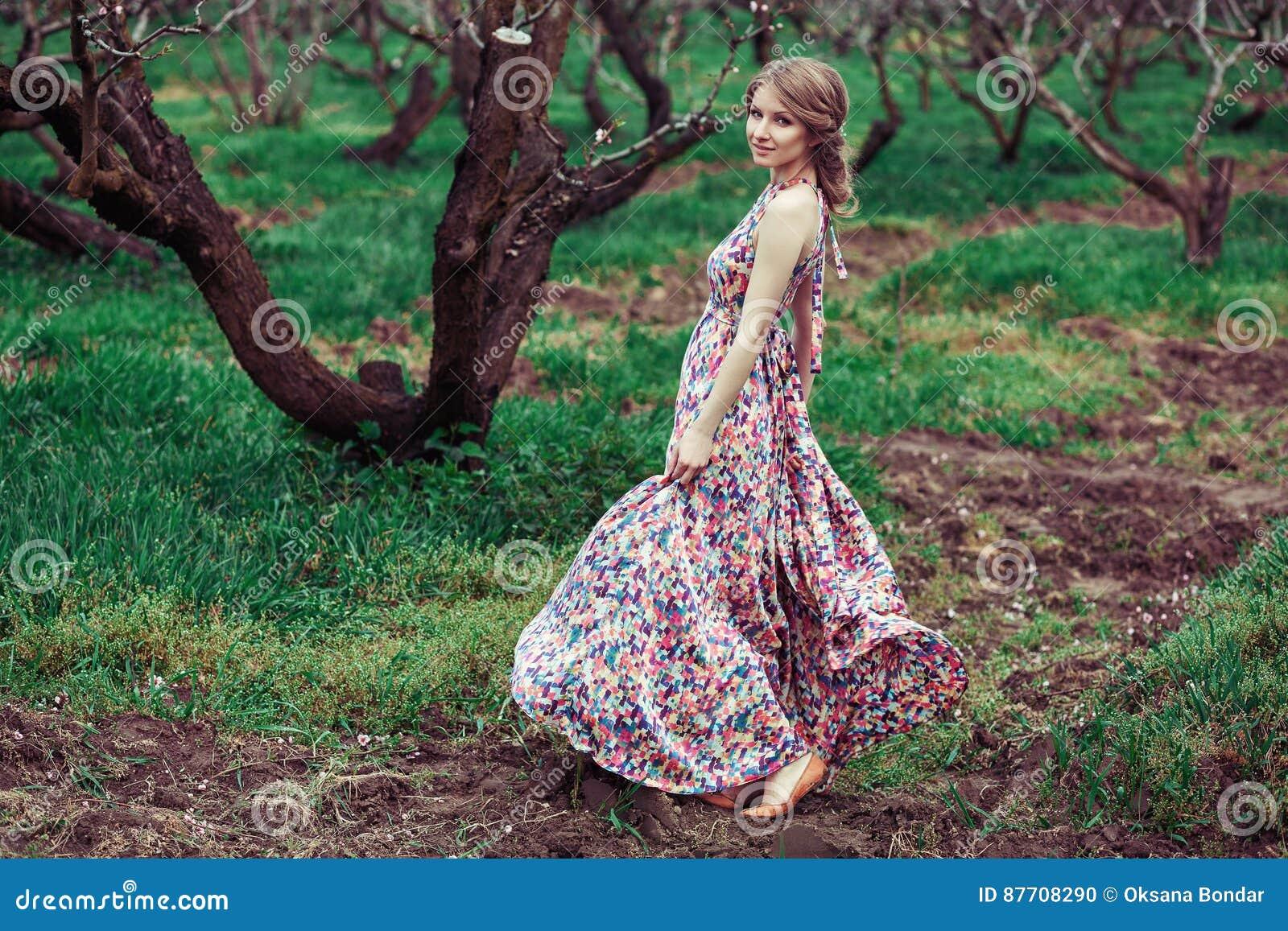 Portrait d une jeune femme blonde sur un fond des arbres fleurissants Rotation de fille robe rose flottant dans le vent