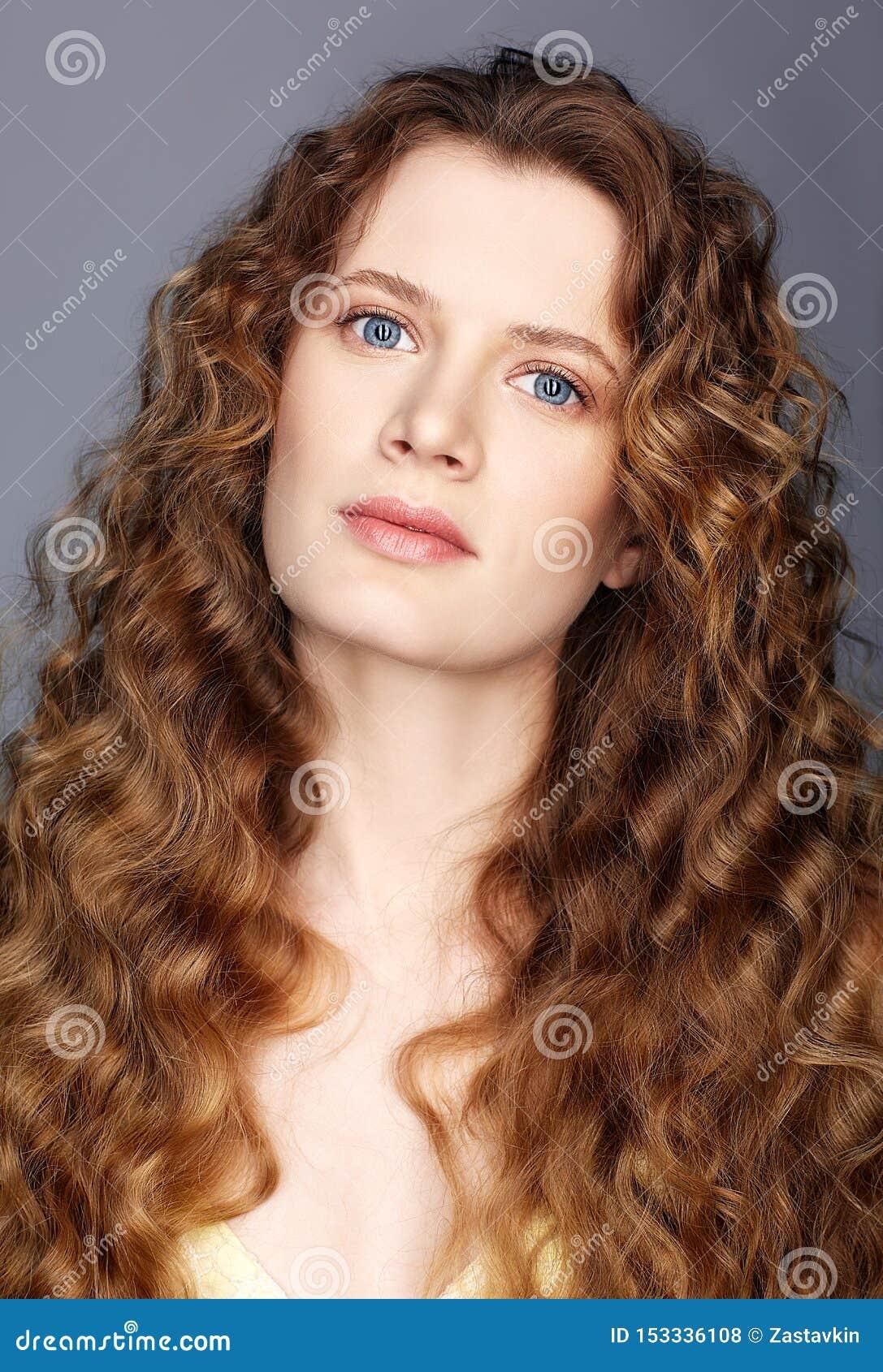 Portrait d une jeune femme caucasienne avec de longs cheveux onduleux d or