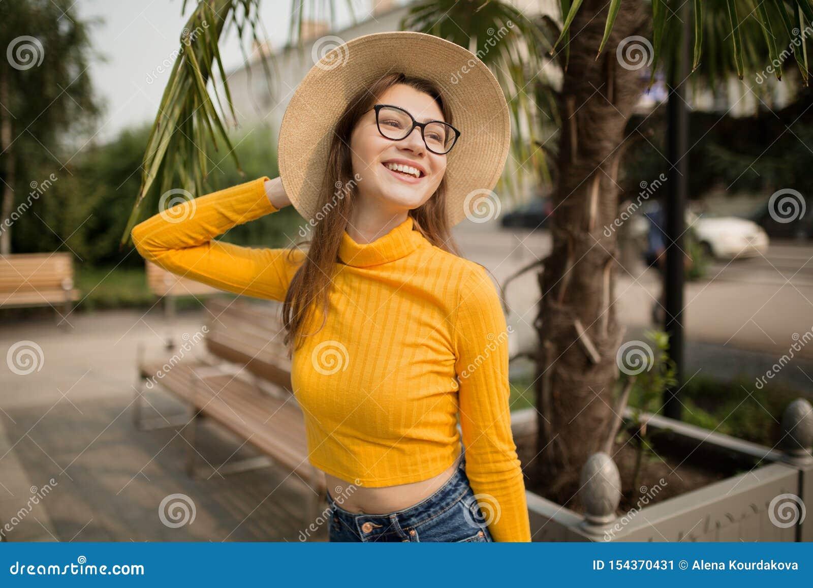 Portrait d une jeune femme dans la ville Palmiers ? l arri?re-plan Femme intelligente heureuse avec le chapeau en verre I