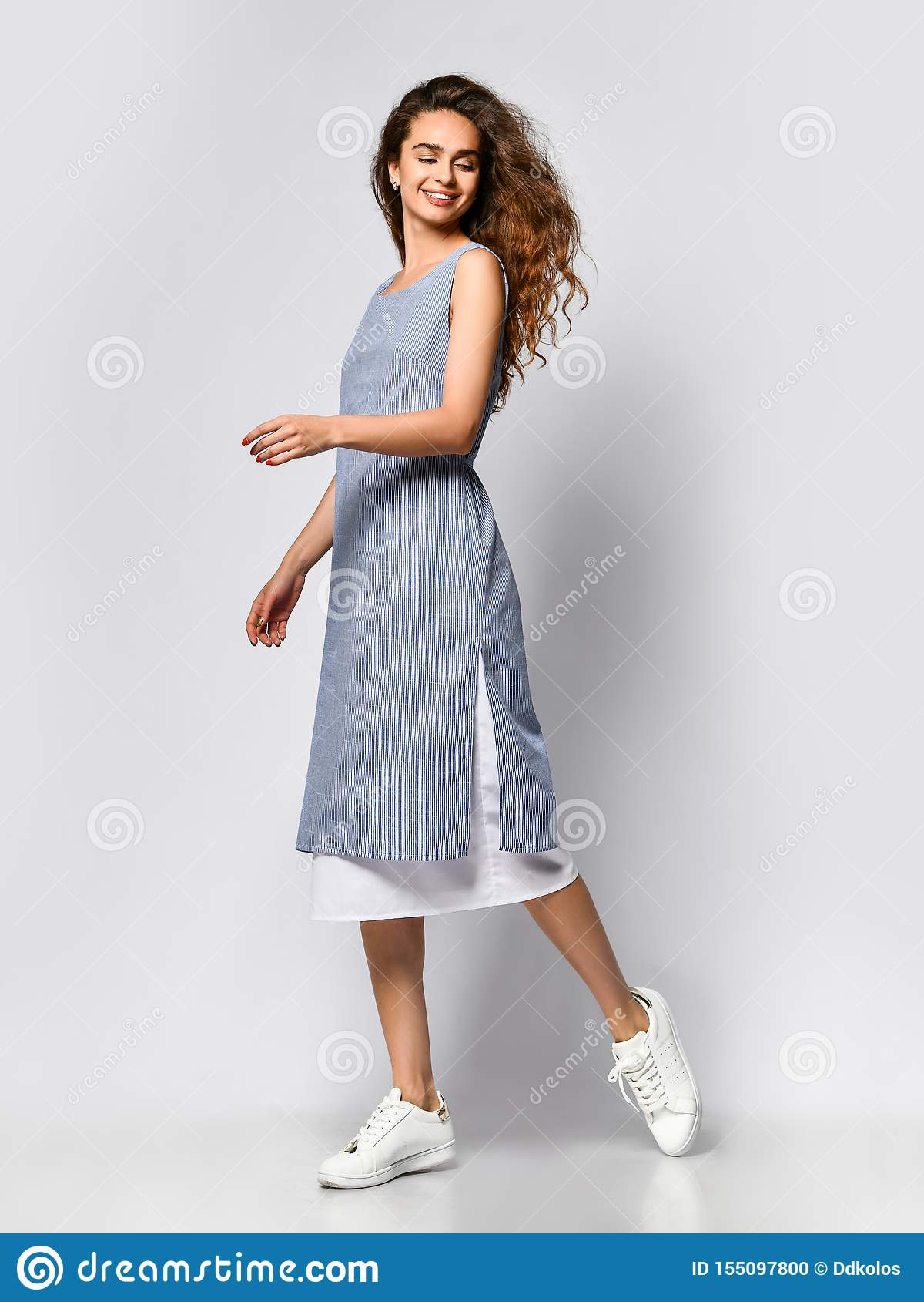 Portrait d une jeune femme de brune dans une robe l?g?re bleue posant sur un fond clair, mode d ?t?, se pr?parant ? une date