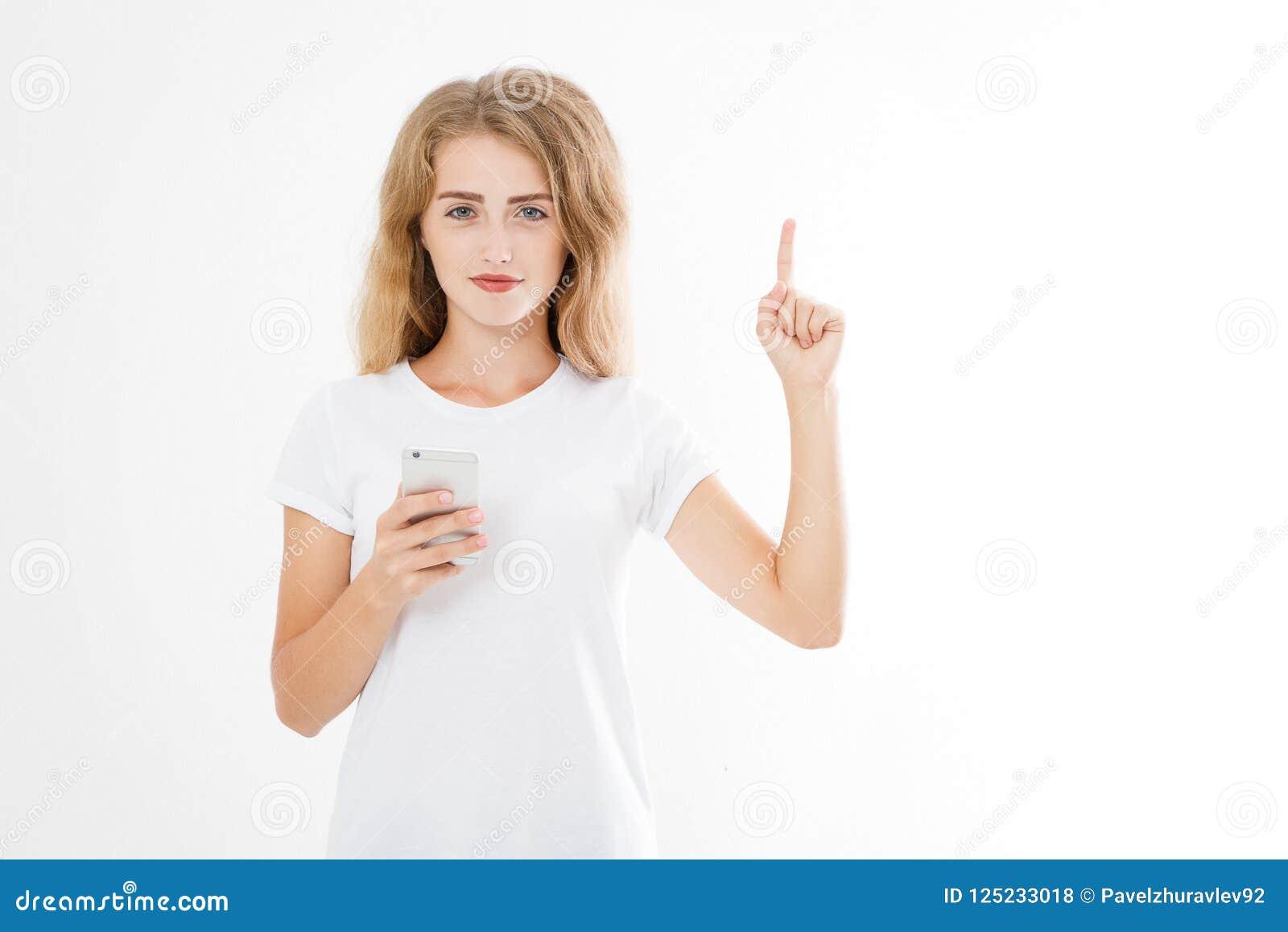 Portrait d une jeune fille de sourire dirigeant le doigt d isolement sur le fond blanc Femme tenant le smartphone Copiez l espace