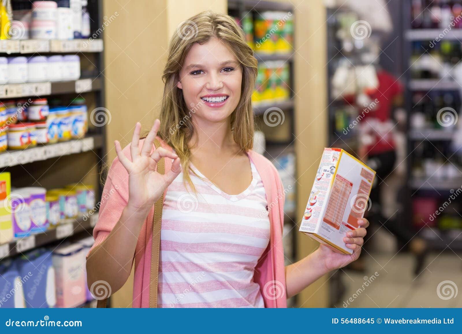 Portrait d une jeune jolie femme de sourire faisant un signe de la main